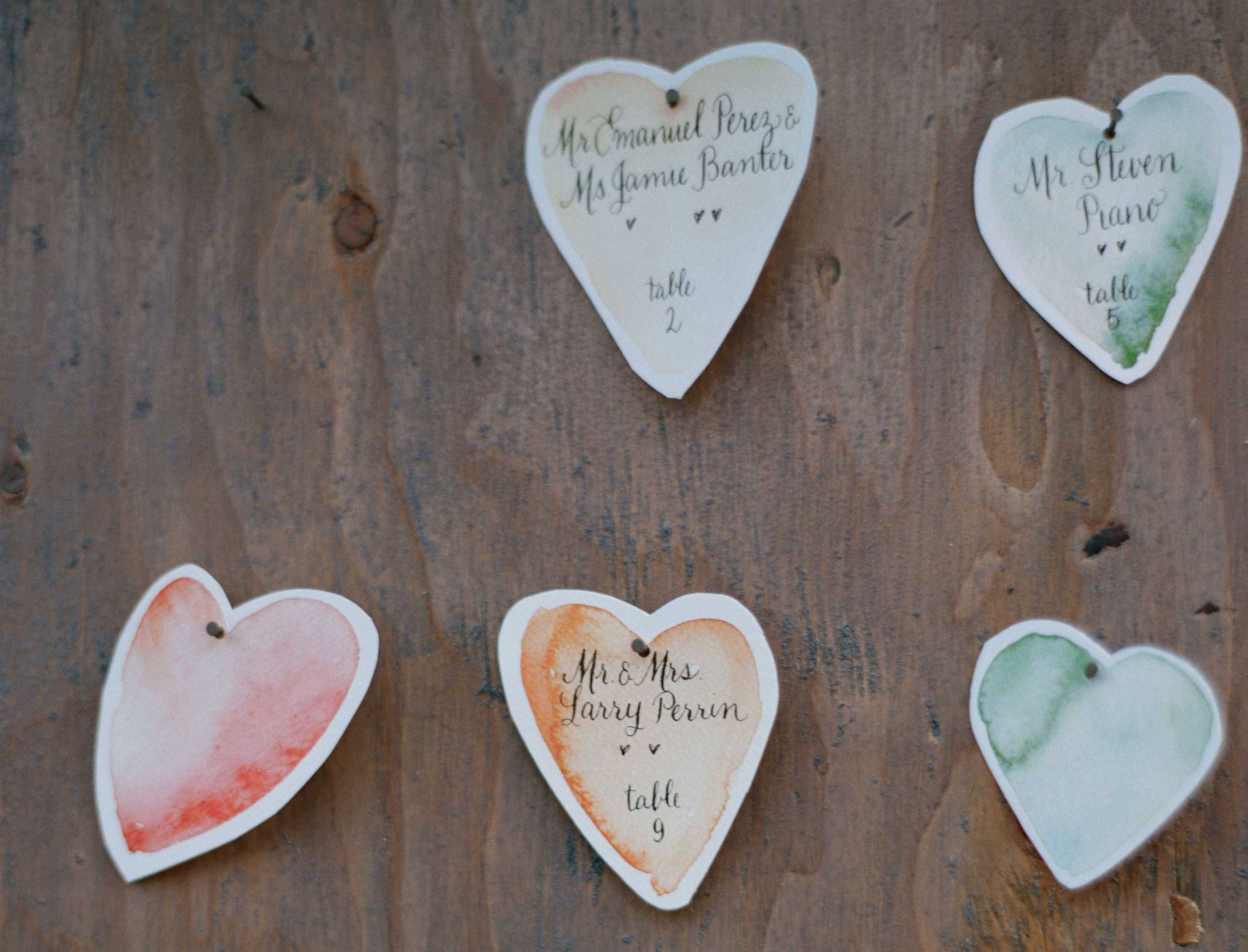 Watercolor heart shape escort cards with calligraphy on wood