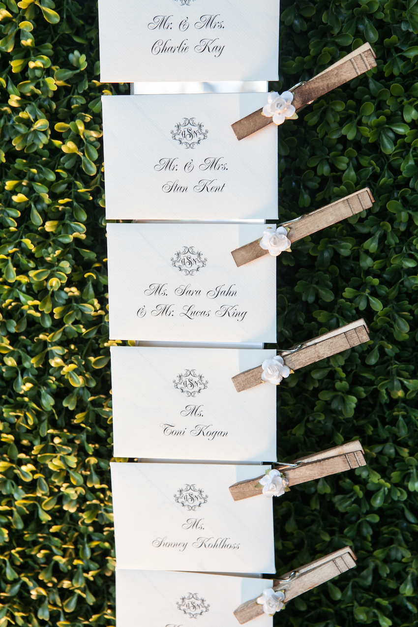 Calligraphy on escort cards attached to hedge with clothespins