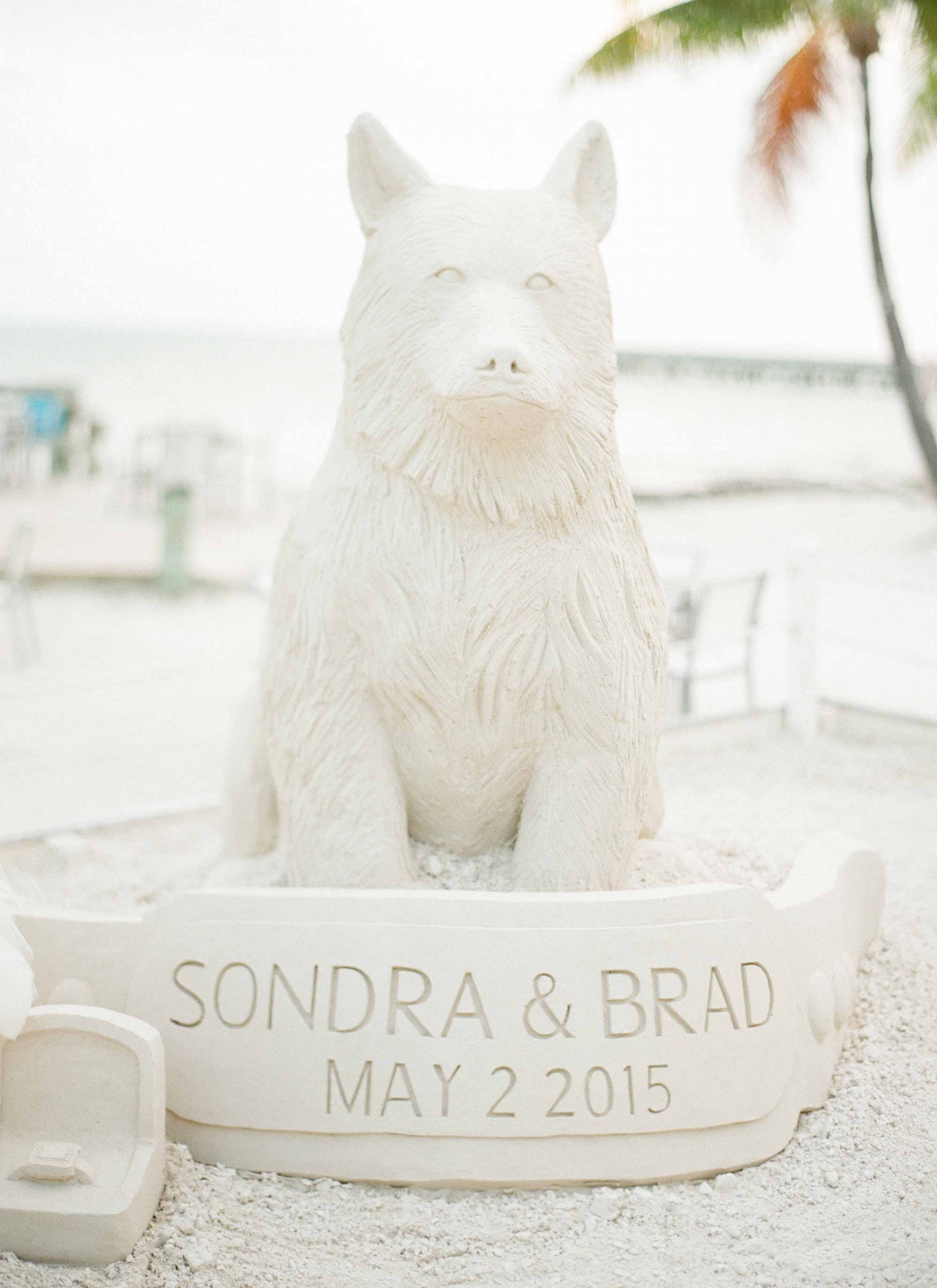 Sand sculpture on beach of dog at wedding