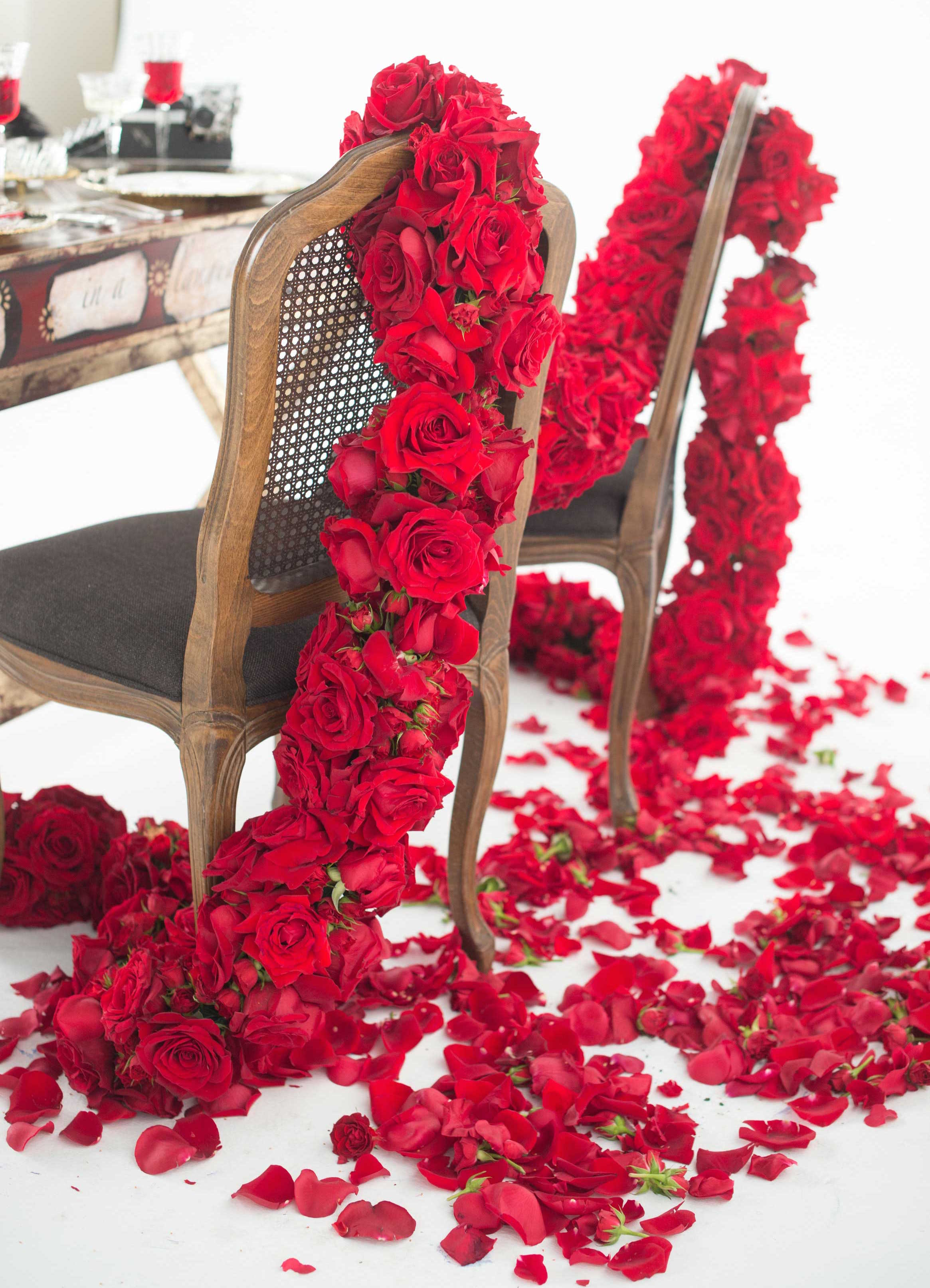 EVOKE DC Love Letters sweetheart table bride groom chairs with garland of red roses petals