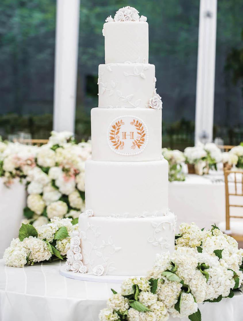 White wedding cake tall with rose gold laurel leaf monogram
