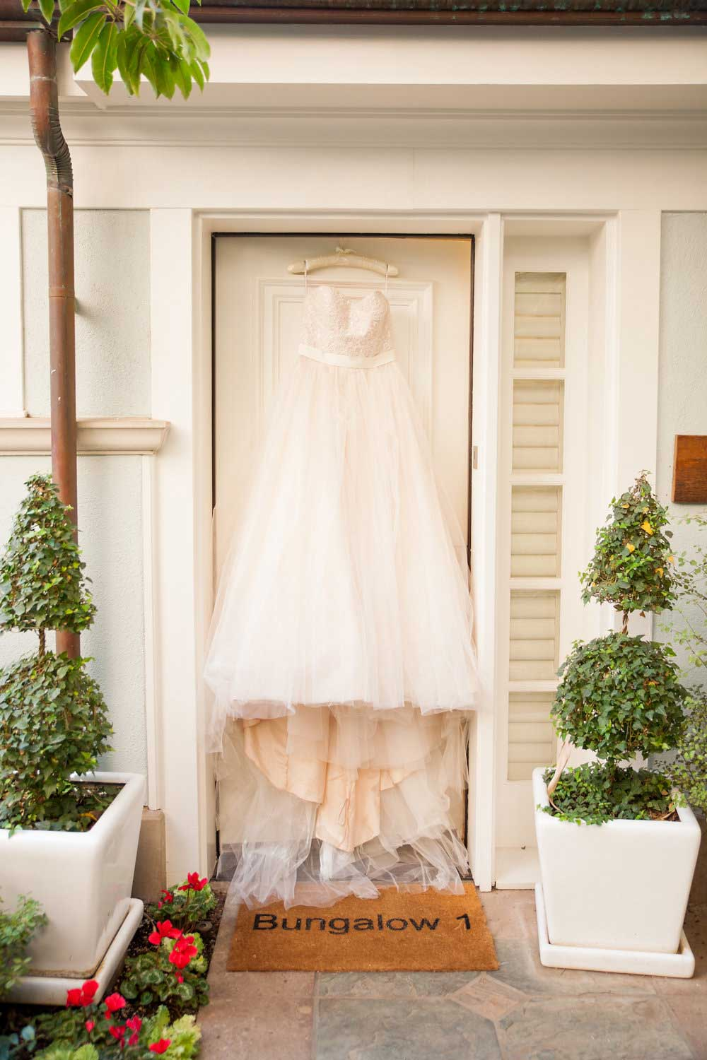 Wedding dress hanging from outside of Fairmont Miramar Hotel & Bungalows room