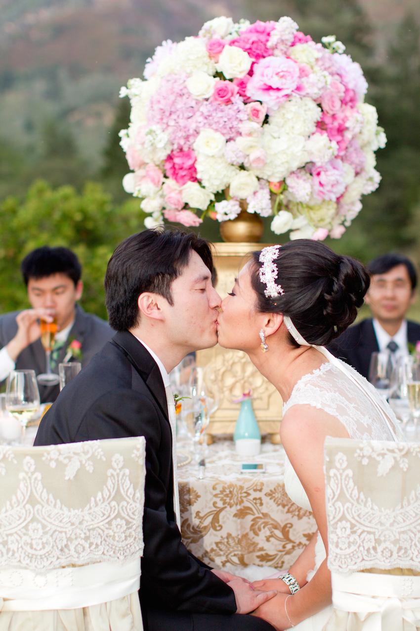 Bride wearing ribbon headband kissing groom