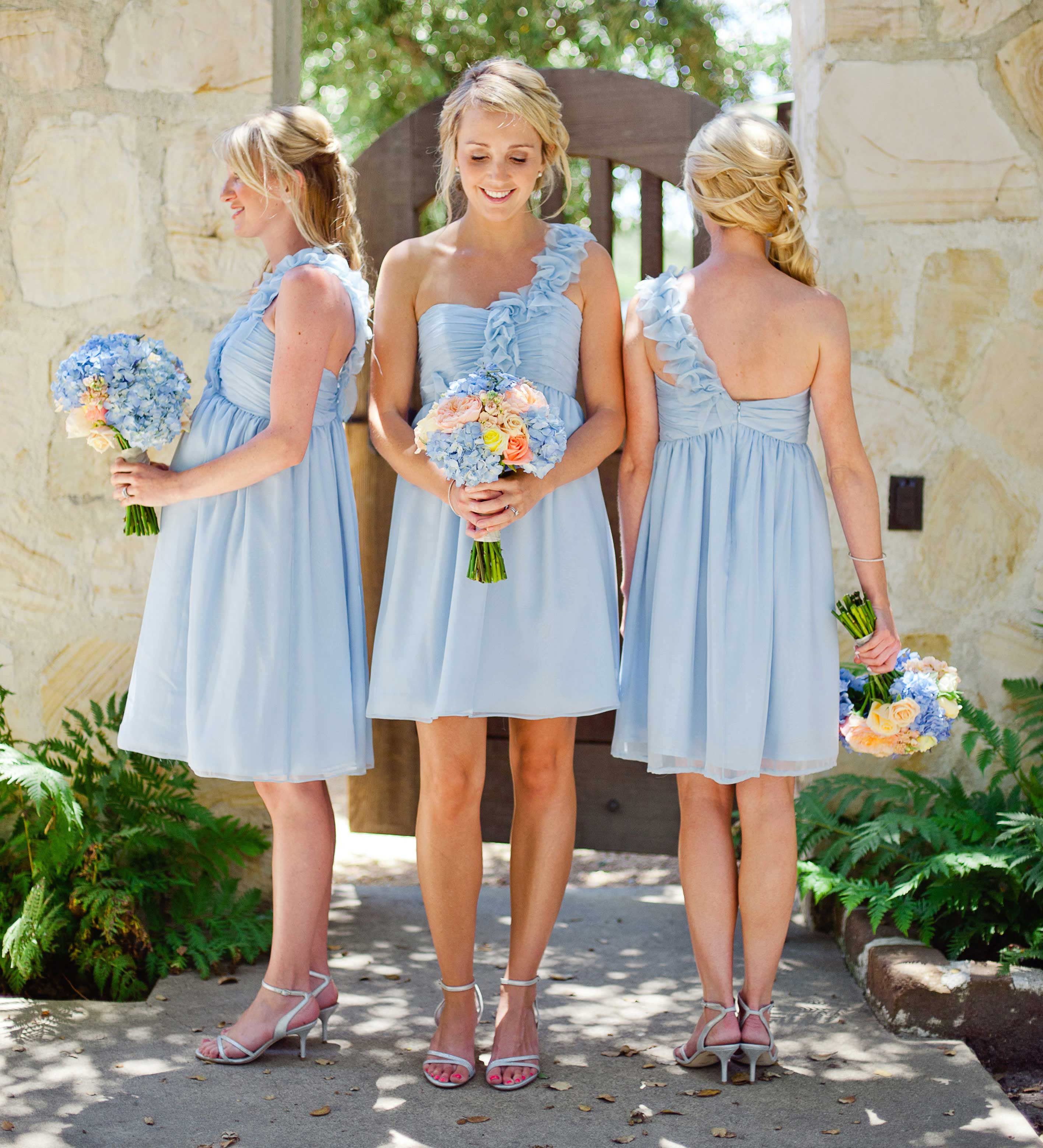 Bridesmaids in short light blue dresses with pastel bouquets
