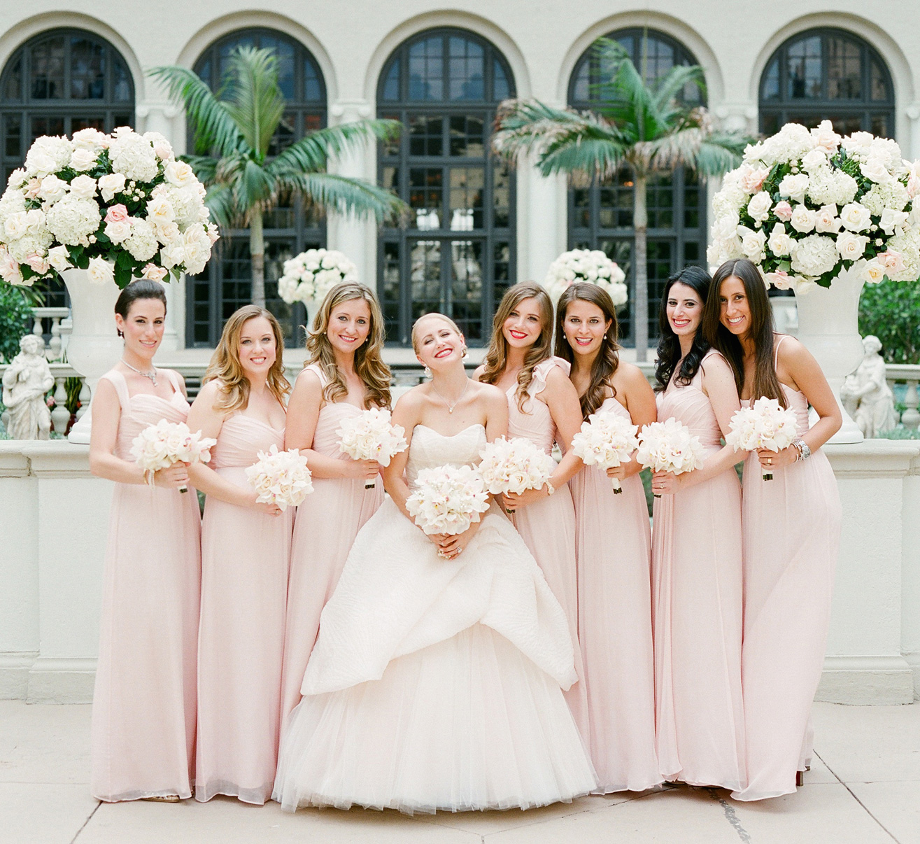Bridesmaids in pink dresses with orchid bouquets