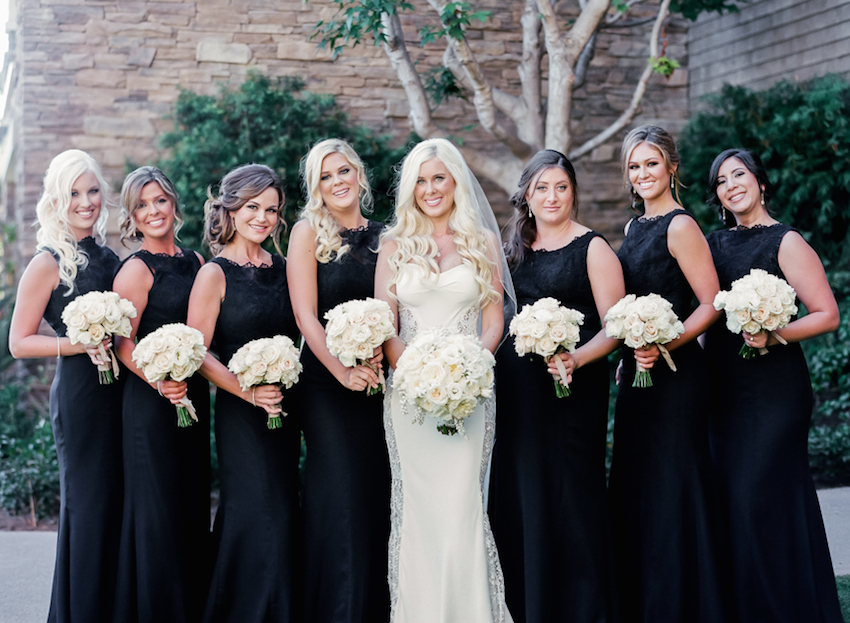 Bridesmaids in black dresses with white bouquets