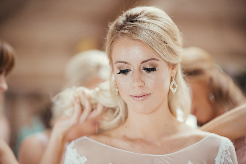 Bride getting ready in bridal suite with help from bridesmaids