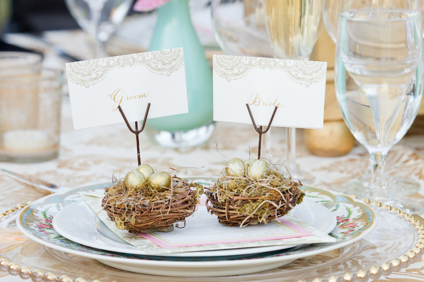 Bride and groom escort cards on table birds nest