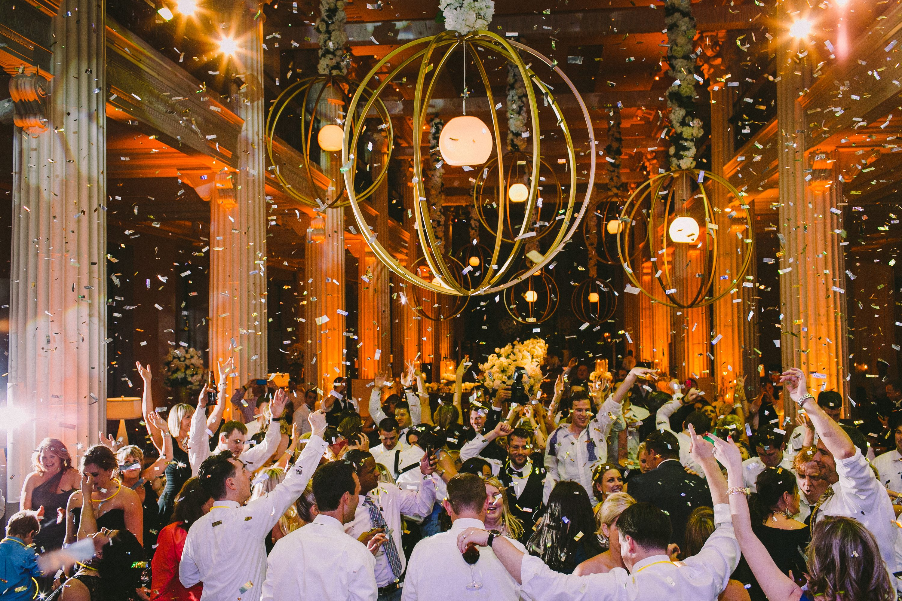 Gold orb over wedding dance floor with metallic confetti