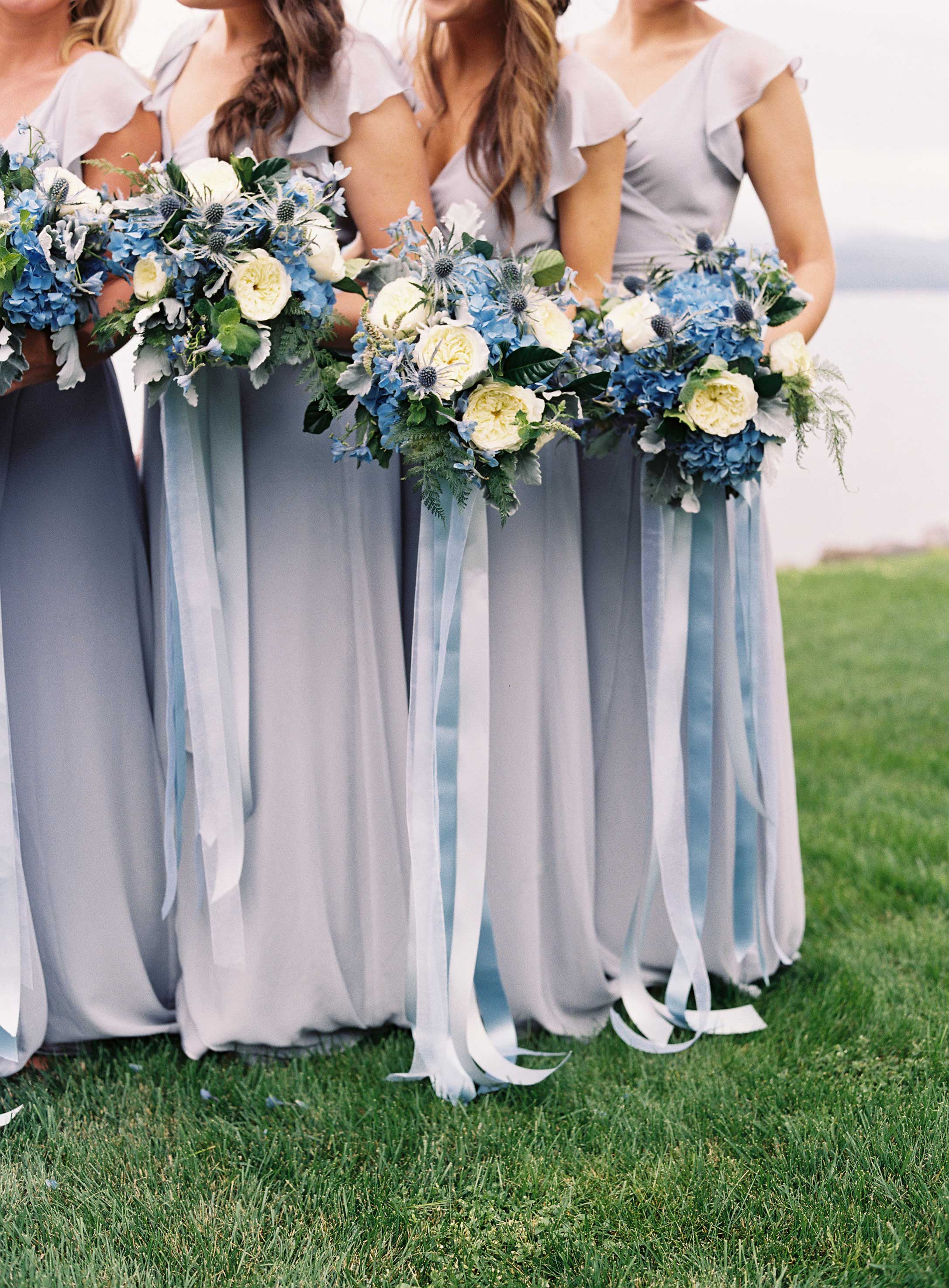Bridesmaids in light blue grey Joanna August bridesmaid dresses with thistle bouquets