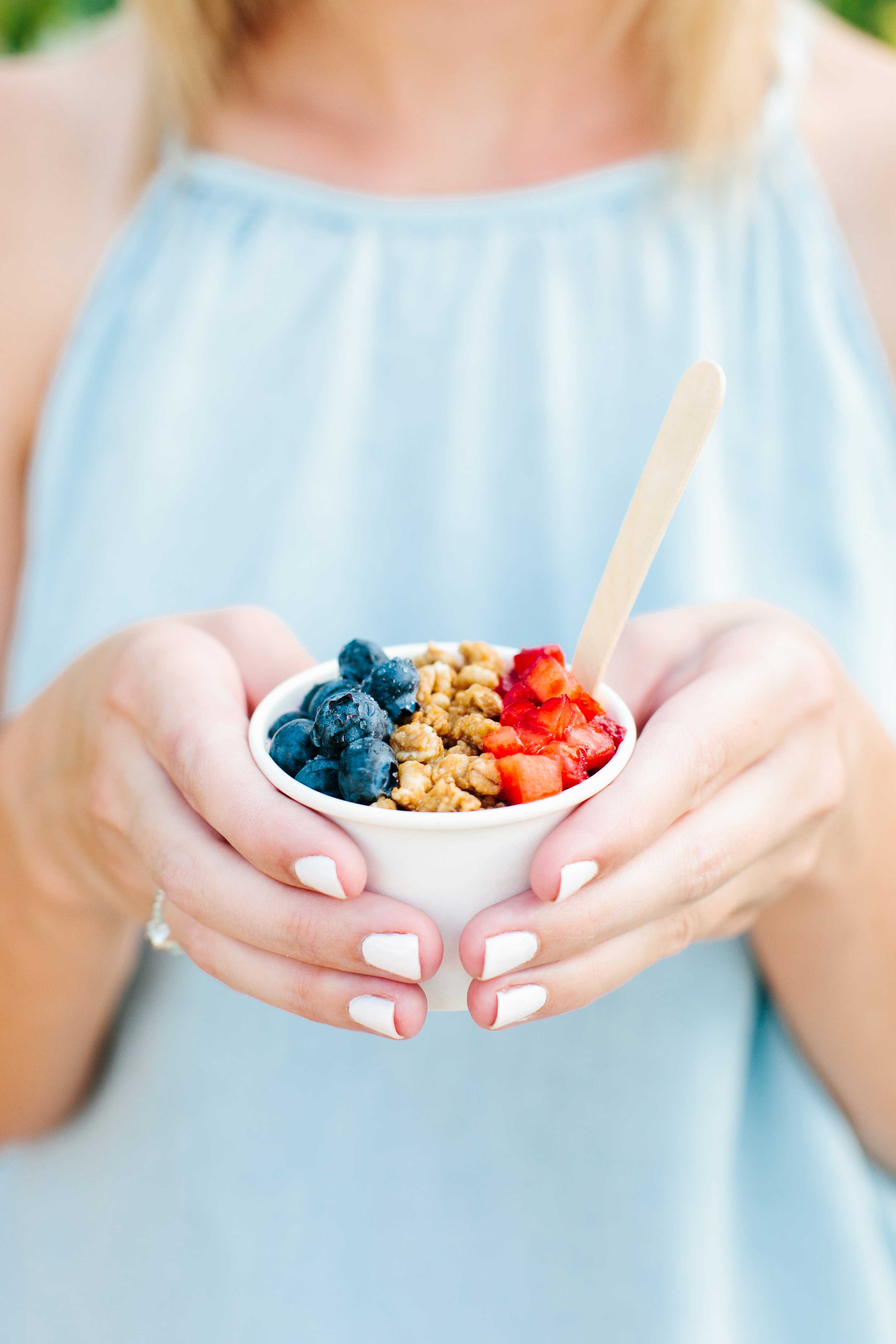Woman in light blue dress and white manicure holding mini smoothie bowl cups