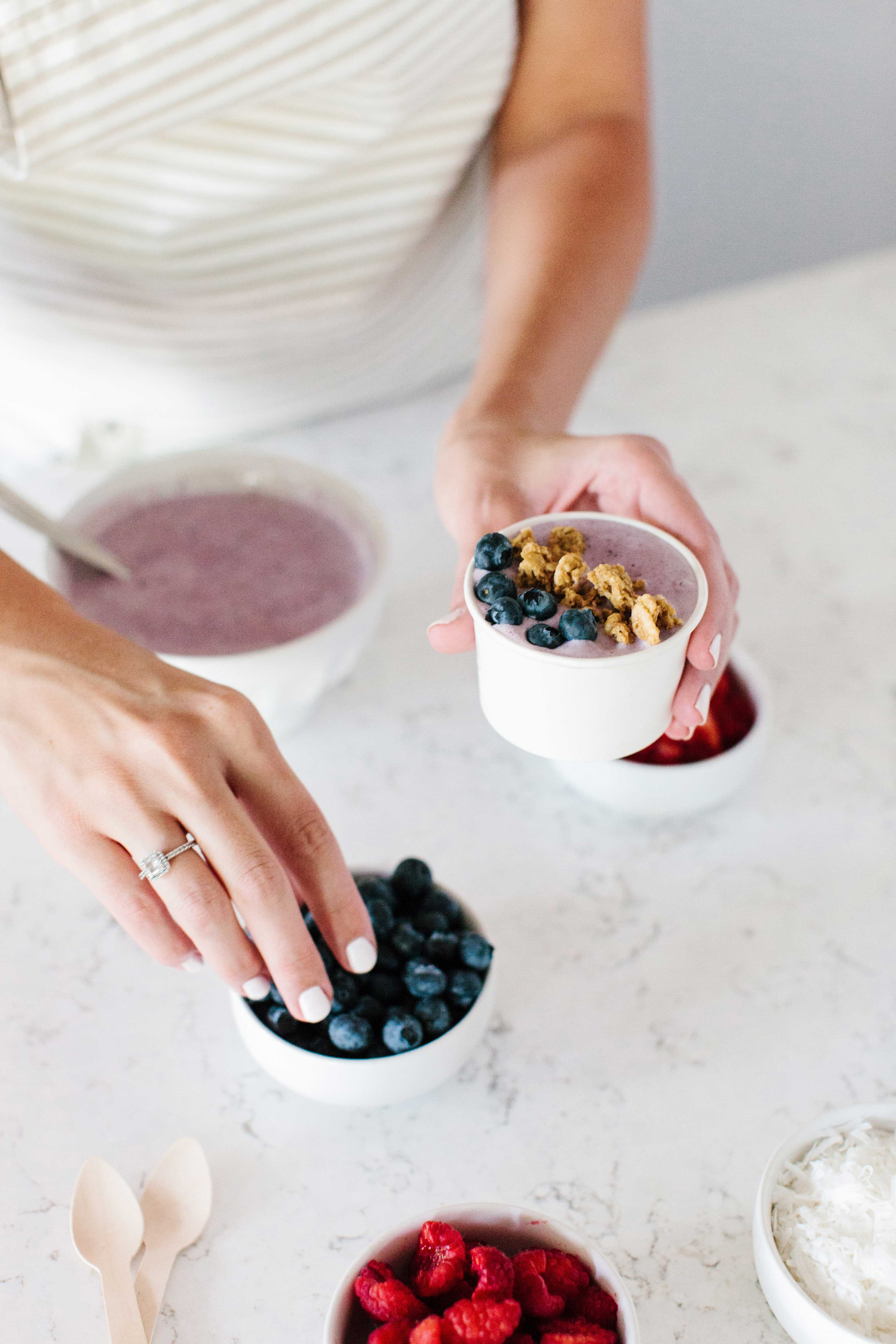 Woman with white manicure making smoothie bowls in kitchen