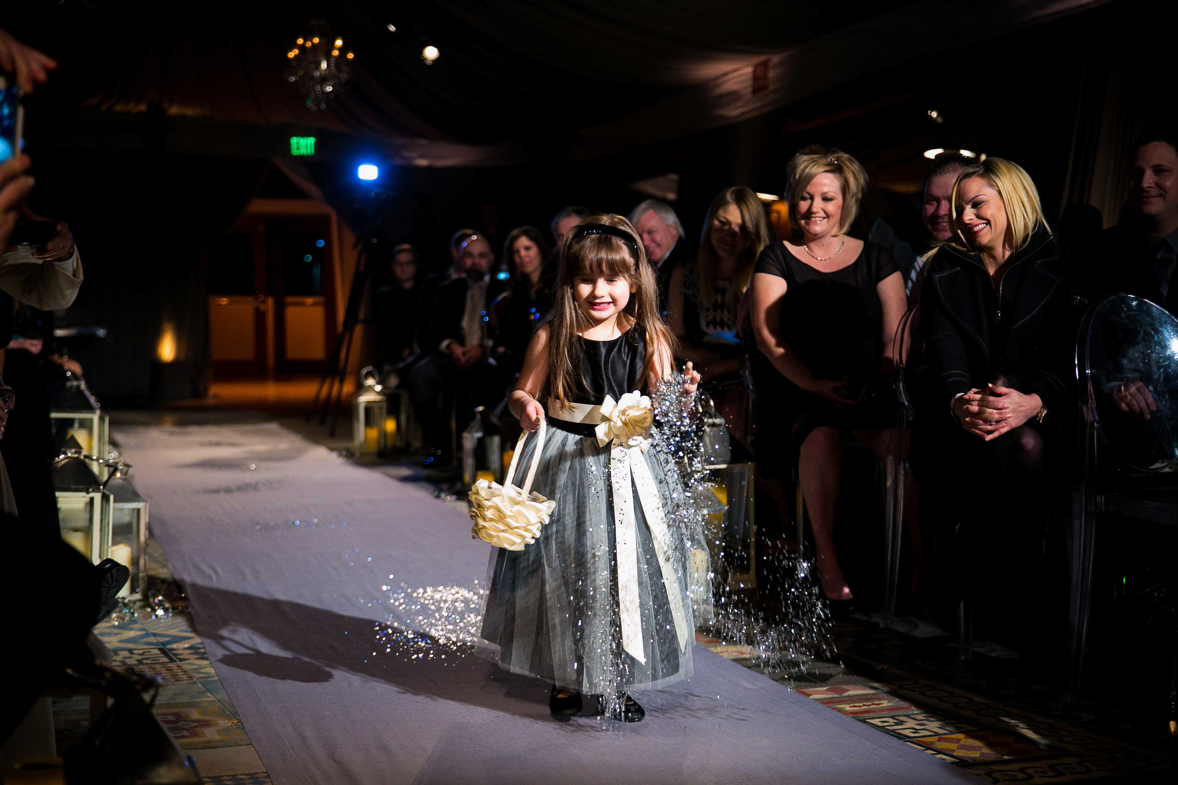 flower girl throws confetti at new year's eve wedding