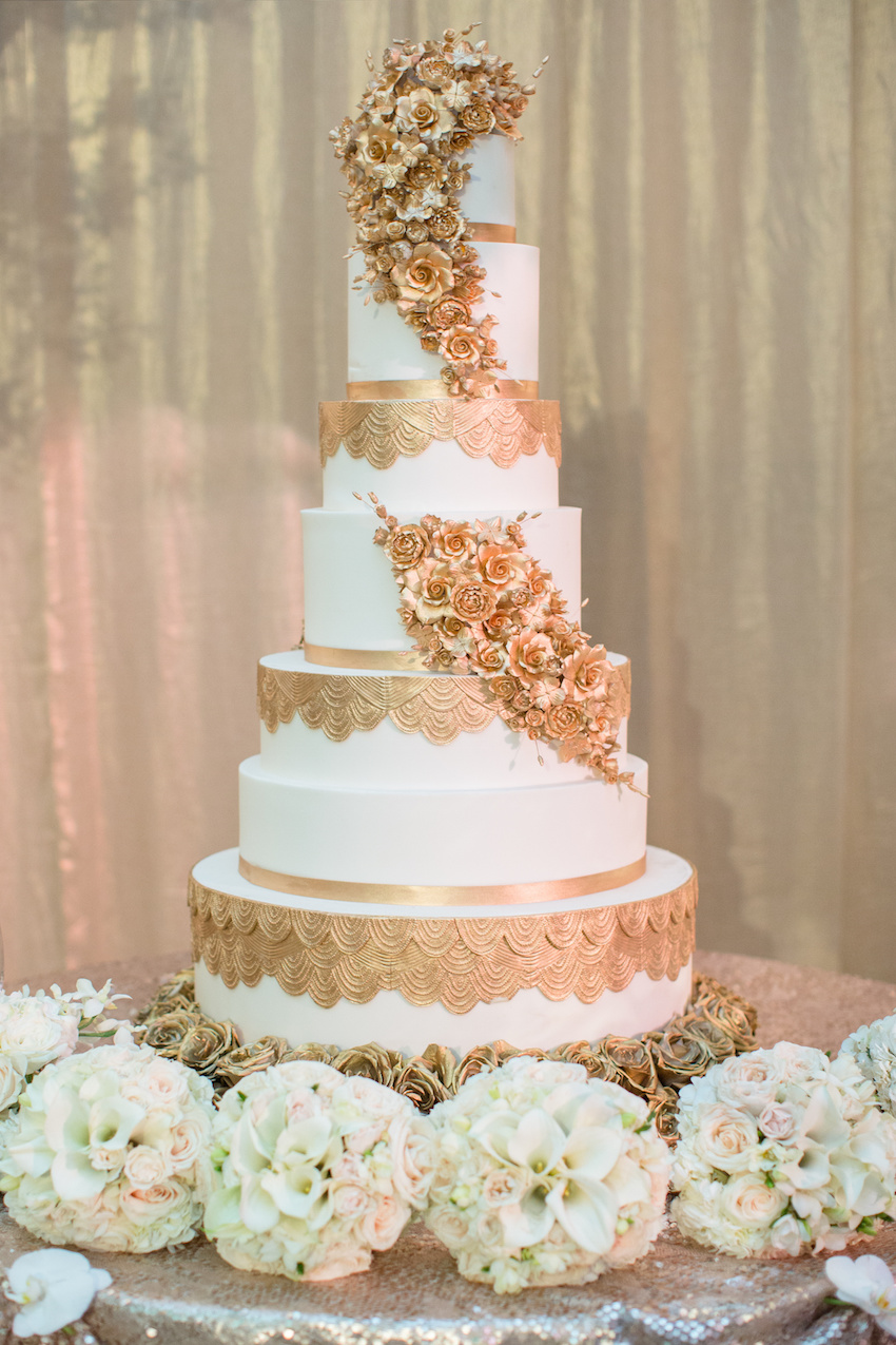 Seven layer wedding cake with white fondant and gold sugar flowers