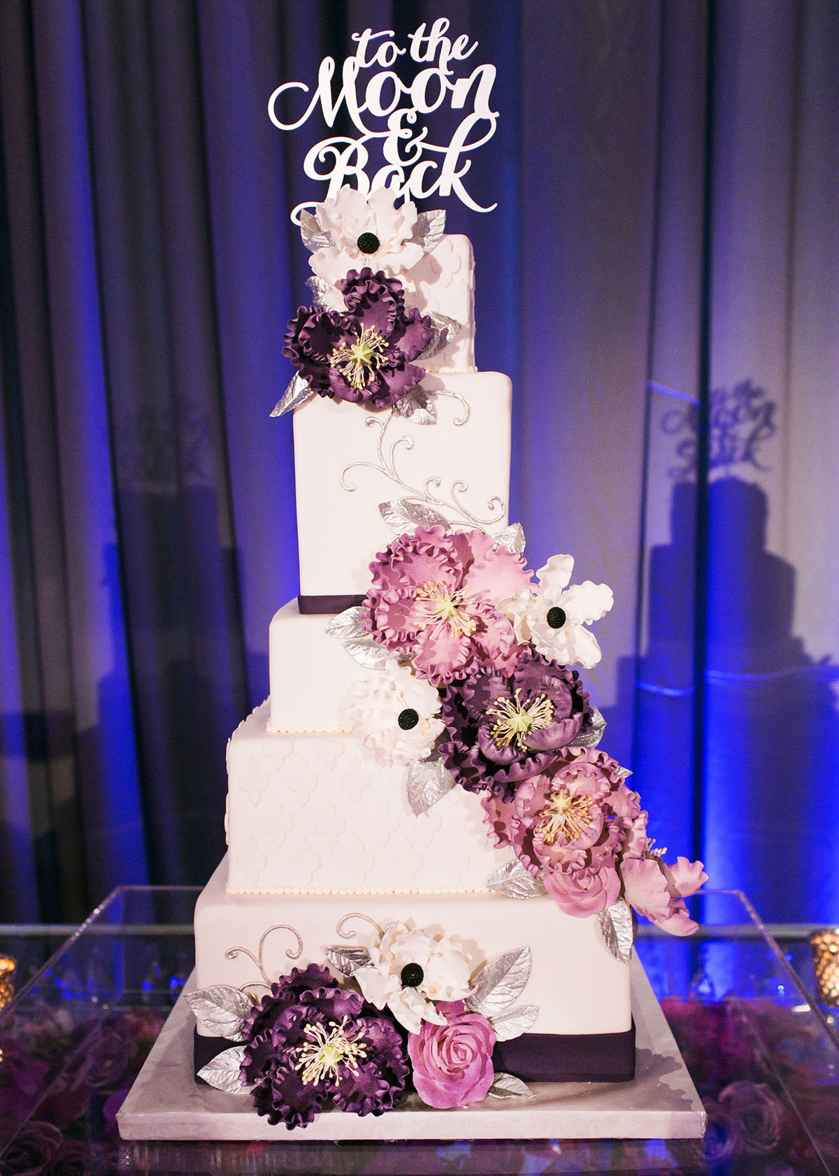White square wedding cake with purple sugar flowers