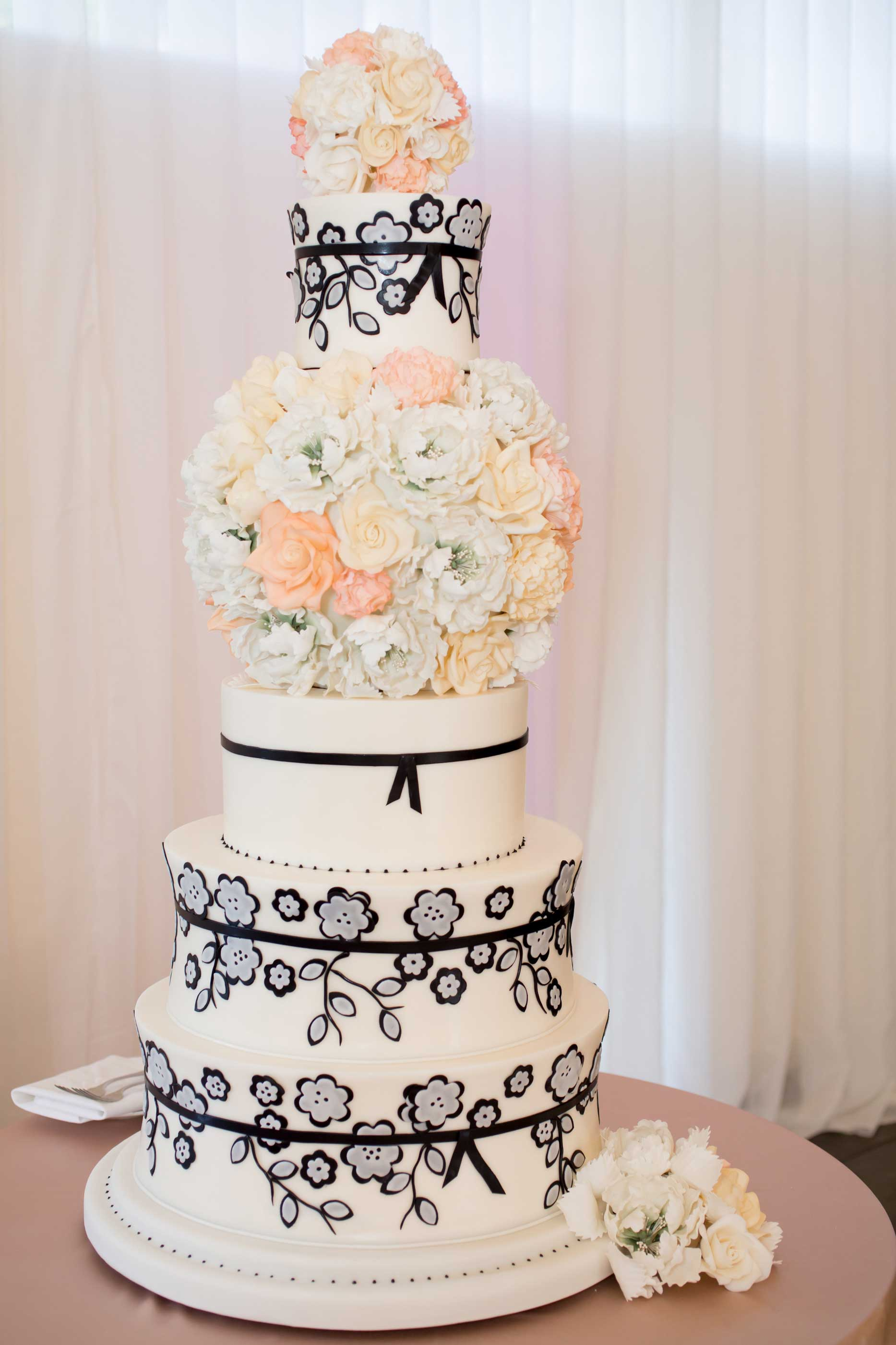 Tall white wedding cake with flower tiers and black flower design
