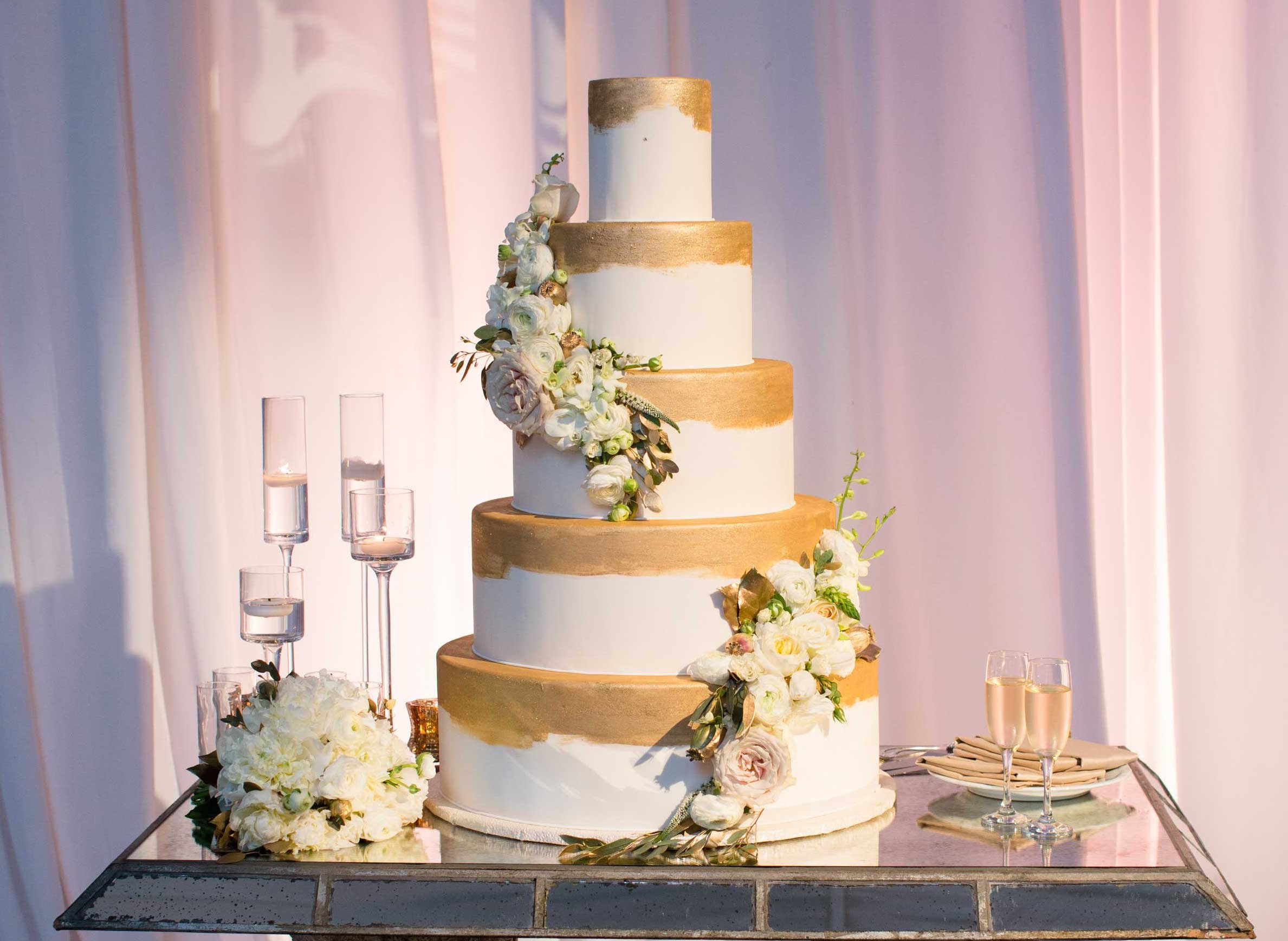 DeMarco Murray five layer wedding cake with white round tiers and gold paint brush strokes