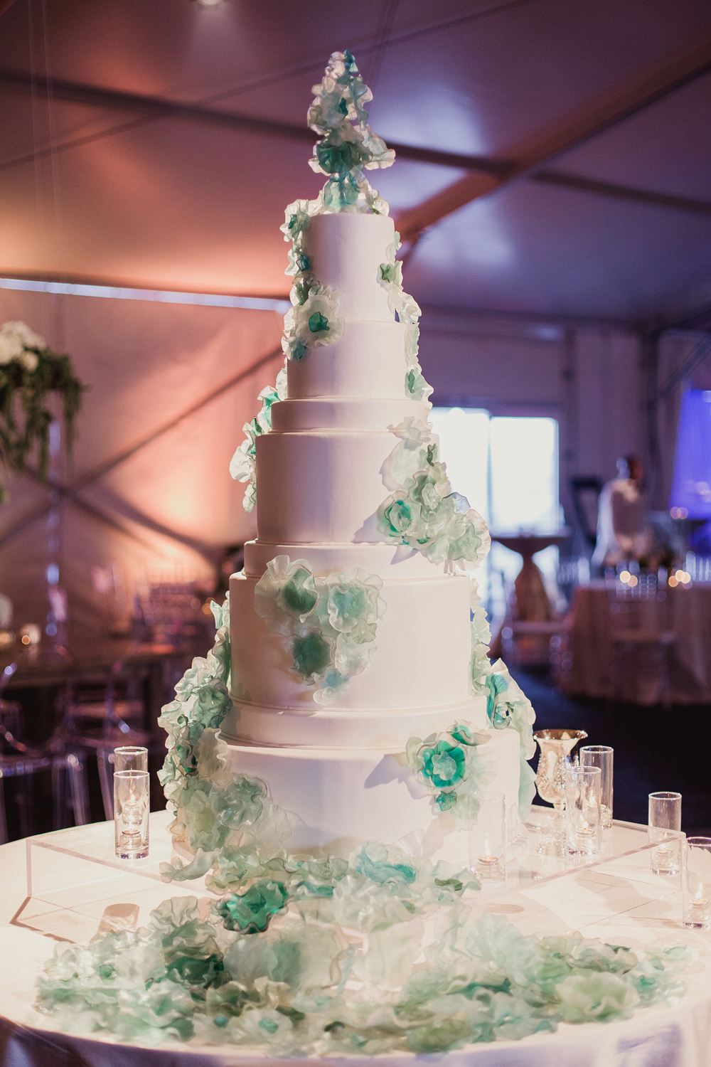 White tall wedding cake with blue and green clear flower designs art inspired