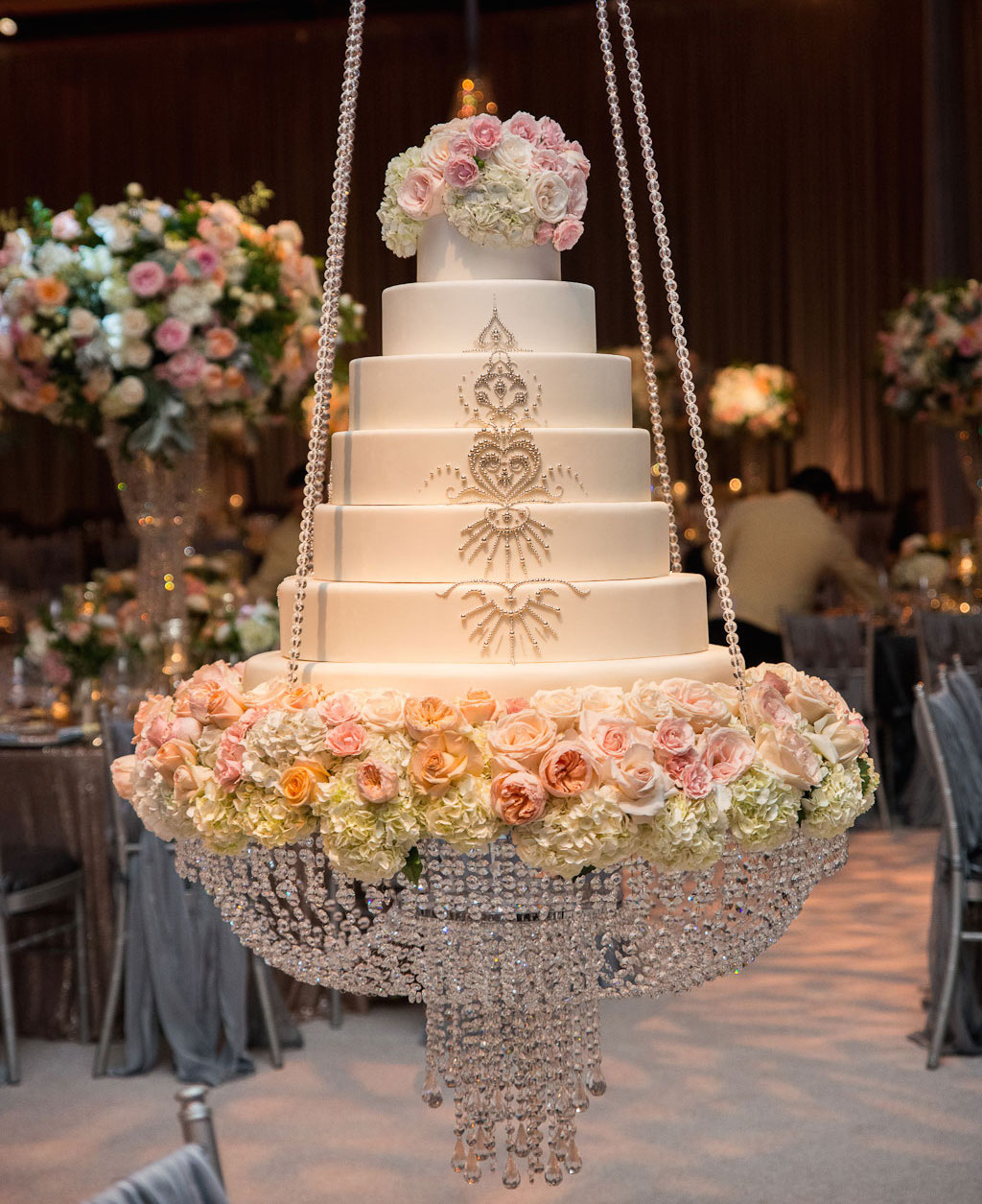 White wedding cake with silver beads on swing at reception