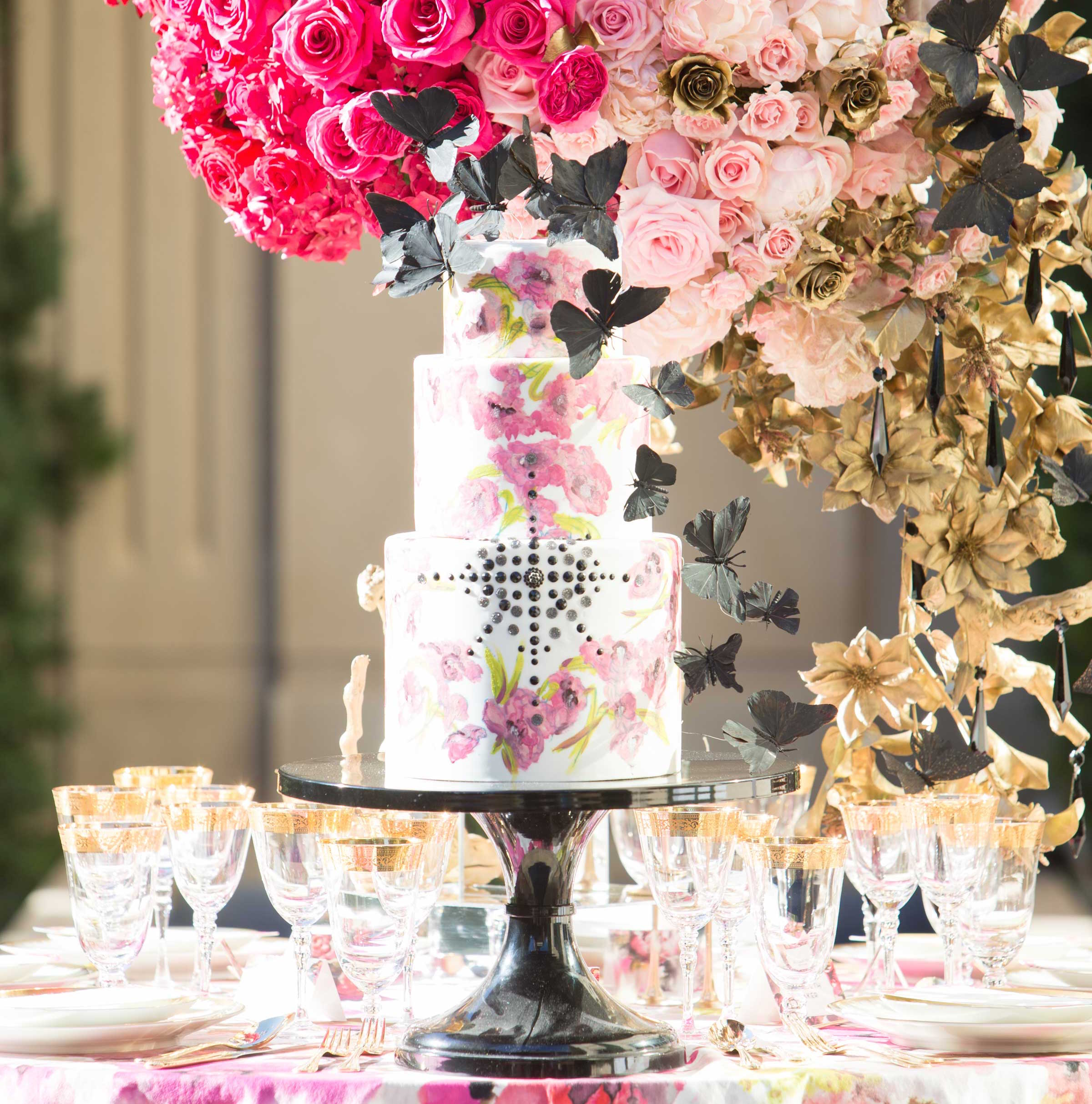 White wedding cake with pink flower watercolor design and black butterfly decals