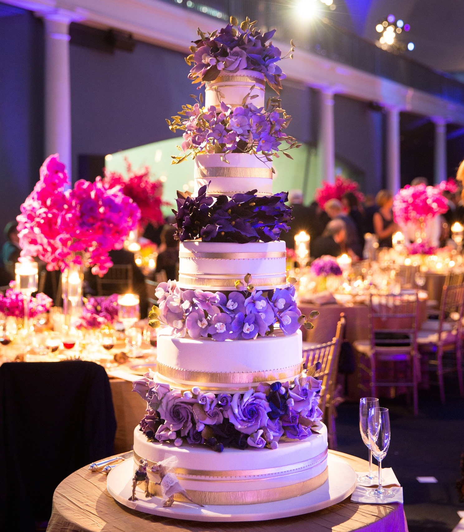 White and gold wedding cake with purple sugar flower tiers