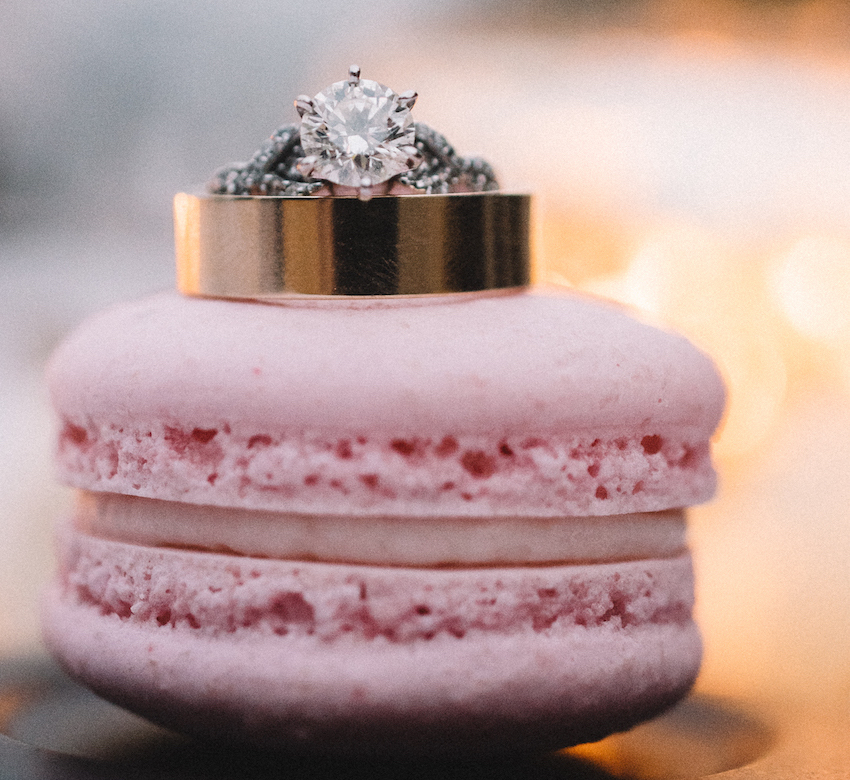 Round six prong engagement ring with twisted band pave diamonds on pink macaron