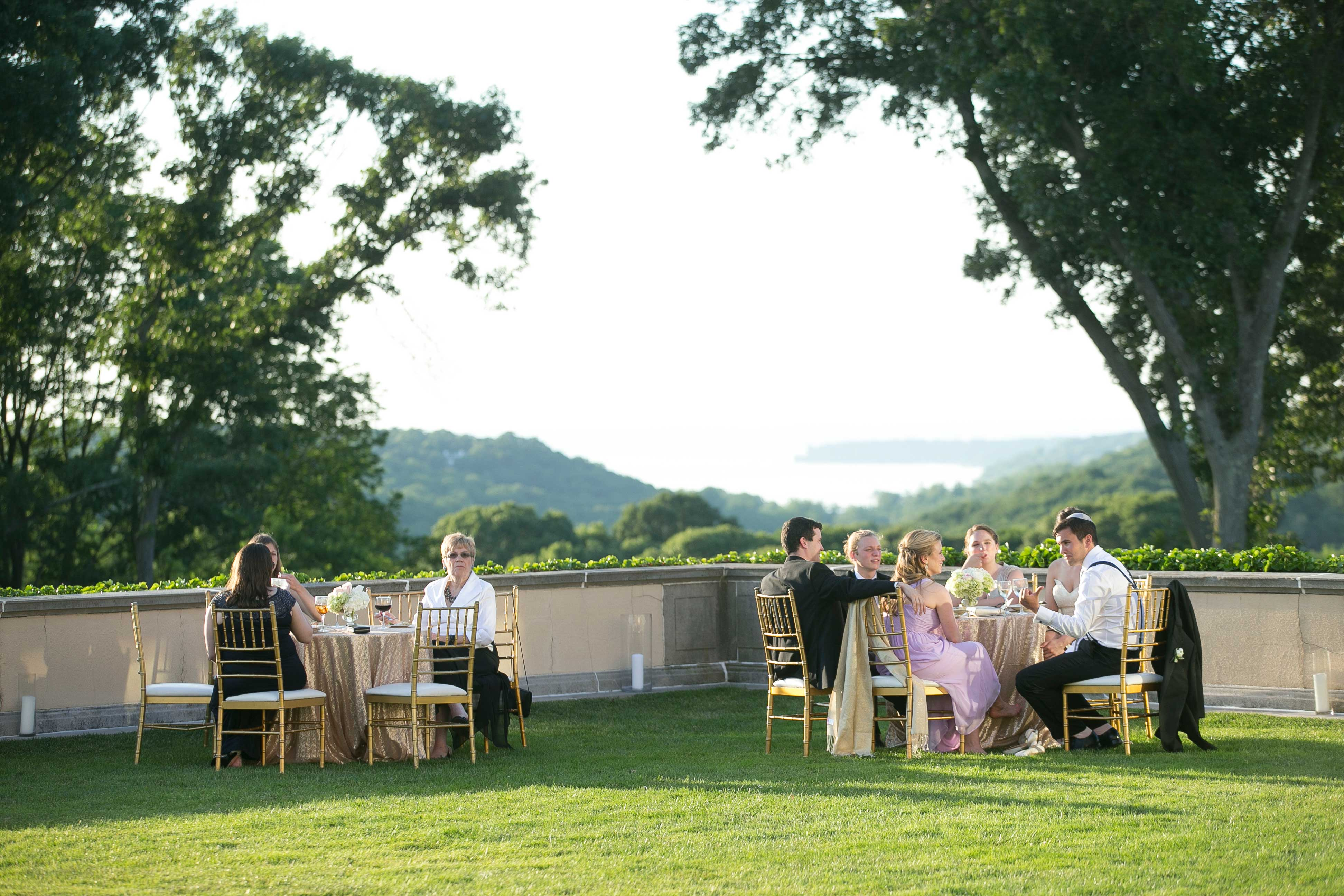 Wedding guests at outdoor cocktail hour on lawn of Oheka Castle