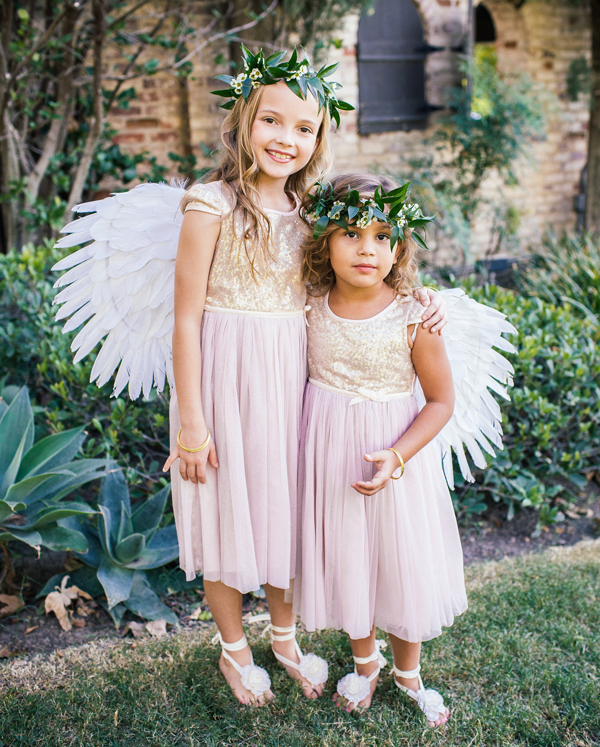 Flower girls in pink and gold sequin dresses with fairy angel wings