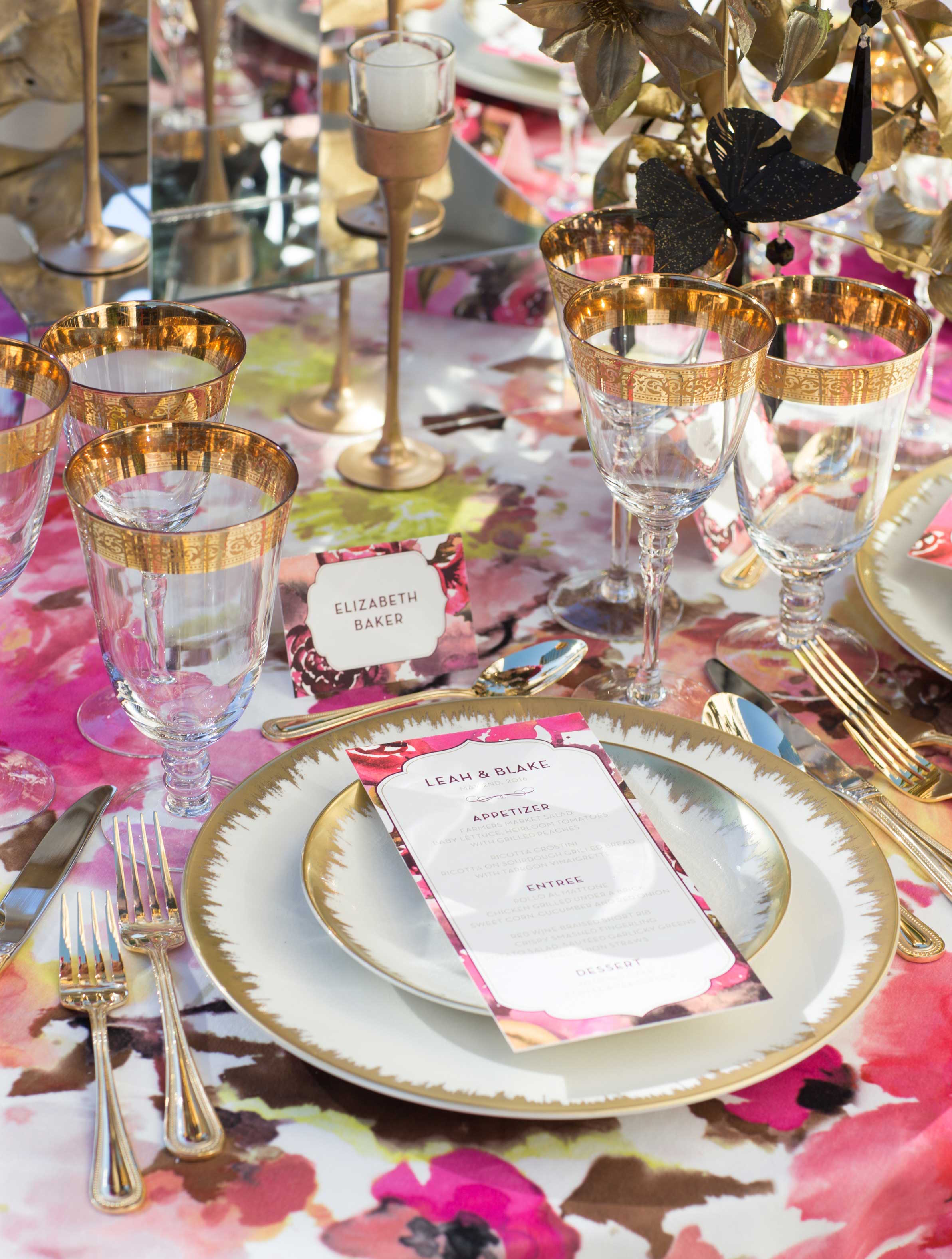 Gold rim glassware and china on pattern pink flower print linen reception styled shoot