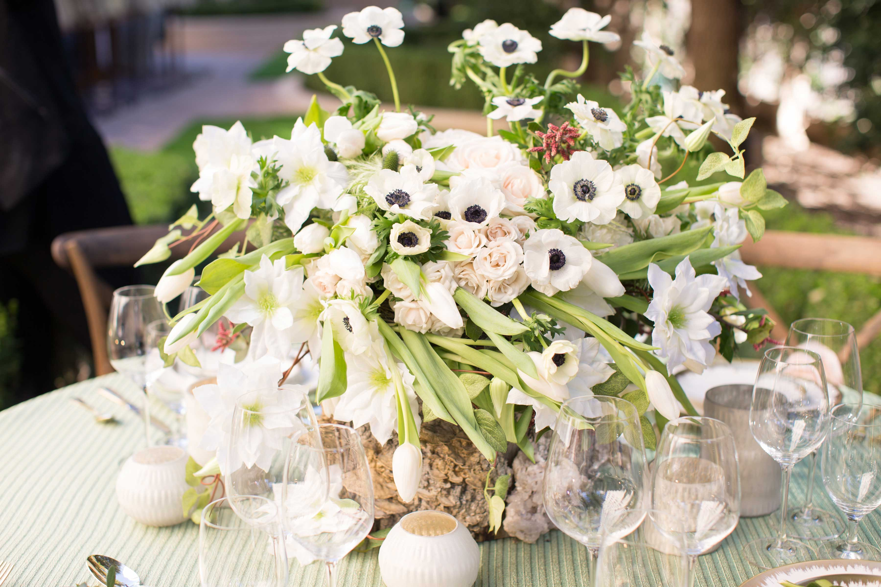 Wood tree stump centerpiece vase with white flowers, anemone blooms