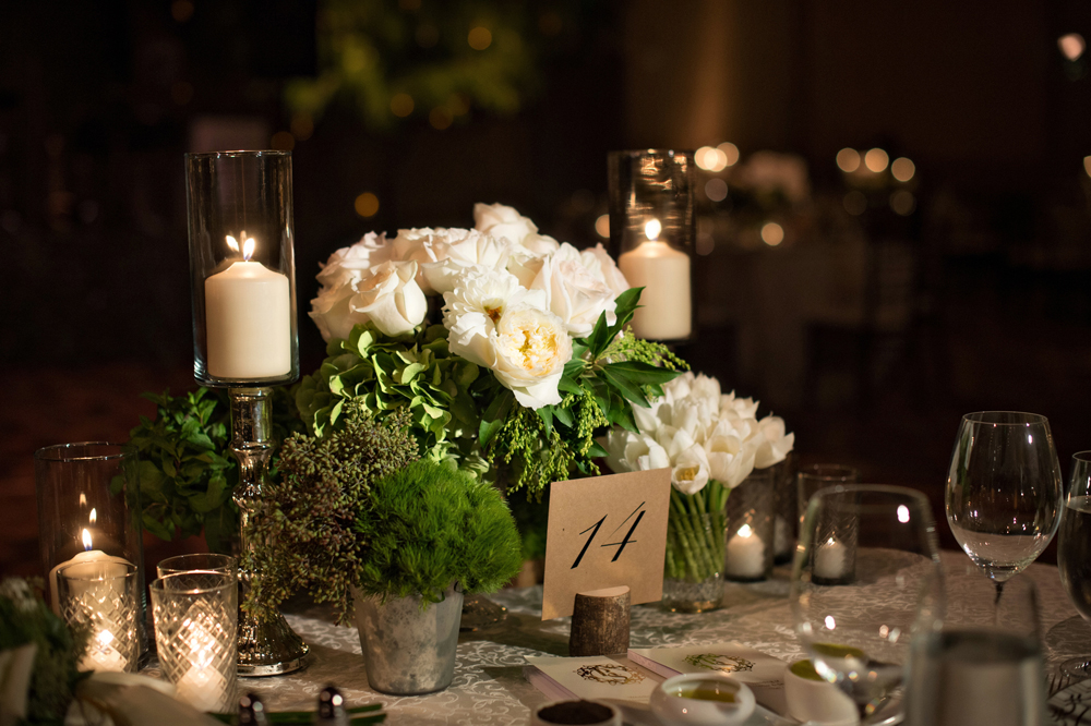 White rose and tulip flowers with green moss and rustic details table number in wood tree trunk