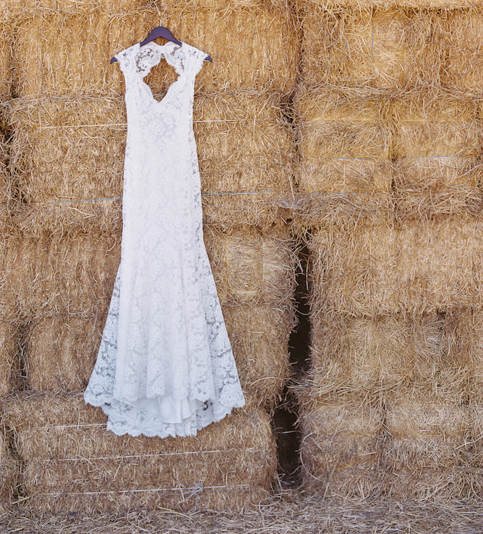 Monique Lhuillier keyhole back lace wedding dress on hay bales