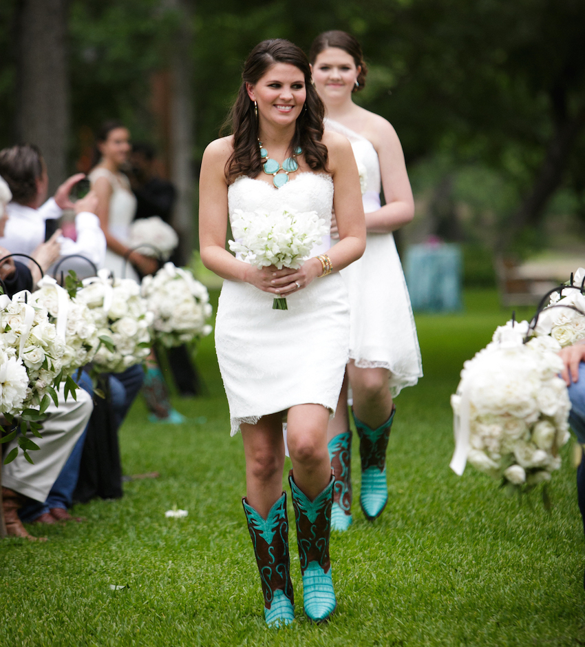 Bridesmaids walking down aisle in short white dresses and cowboy boots