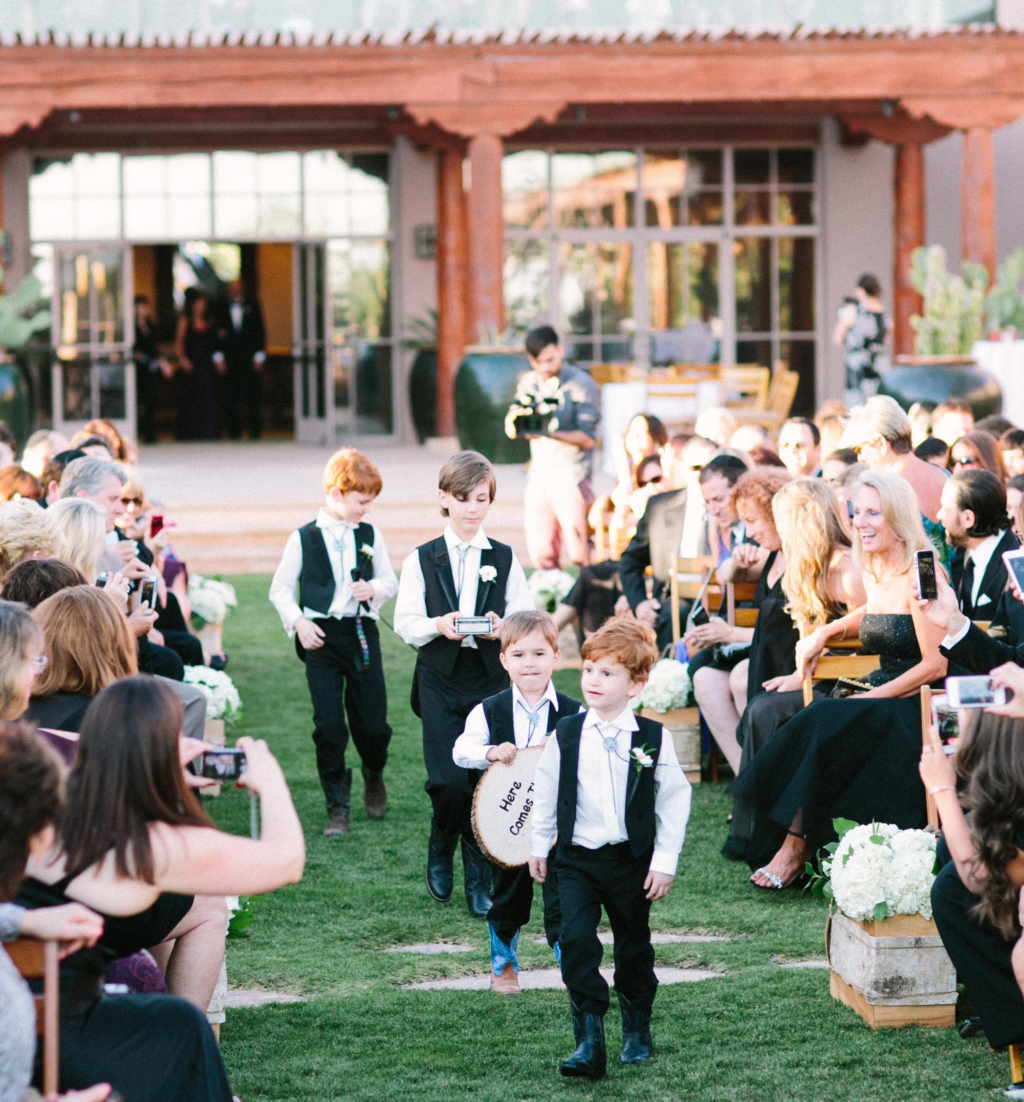 Ring bearers at outdoor rustic wedding in bolo ties, vests, cowboy boots