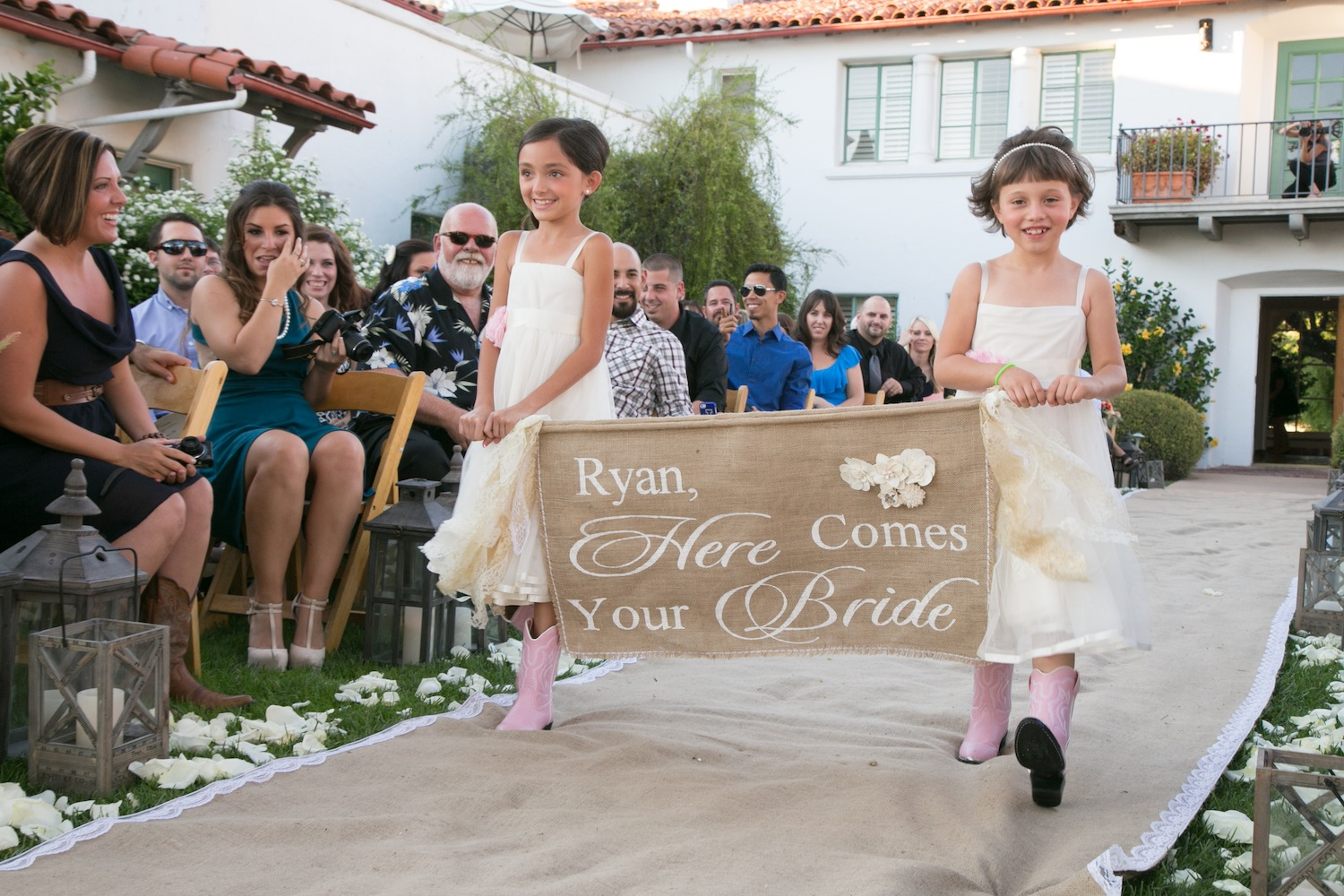 Flower girls in pink cowboy boots, burlap aisle runner, burlap sign David Tutera wedding