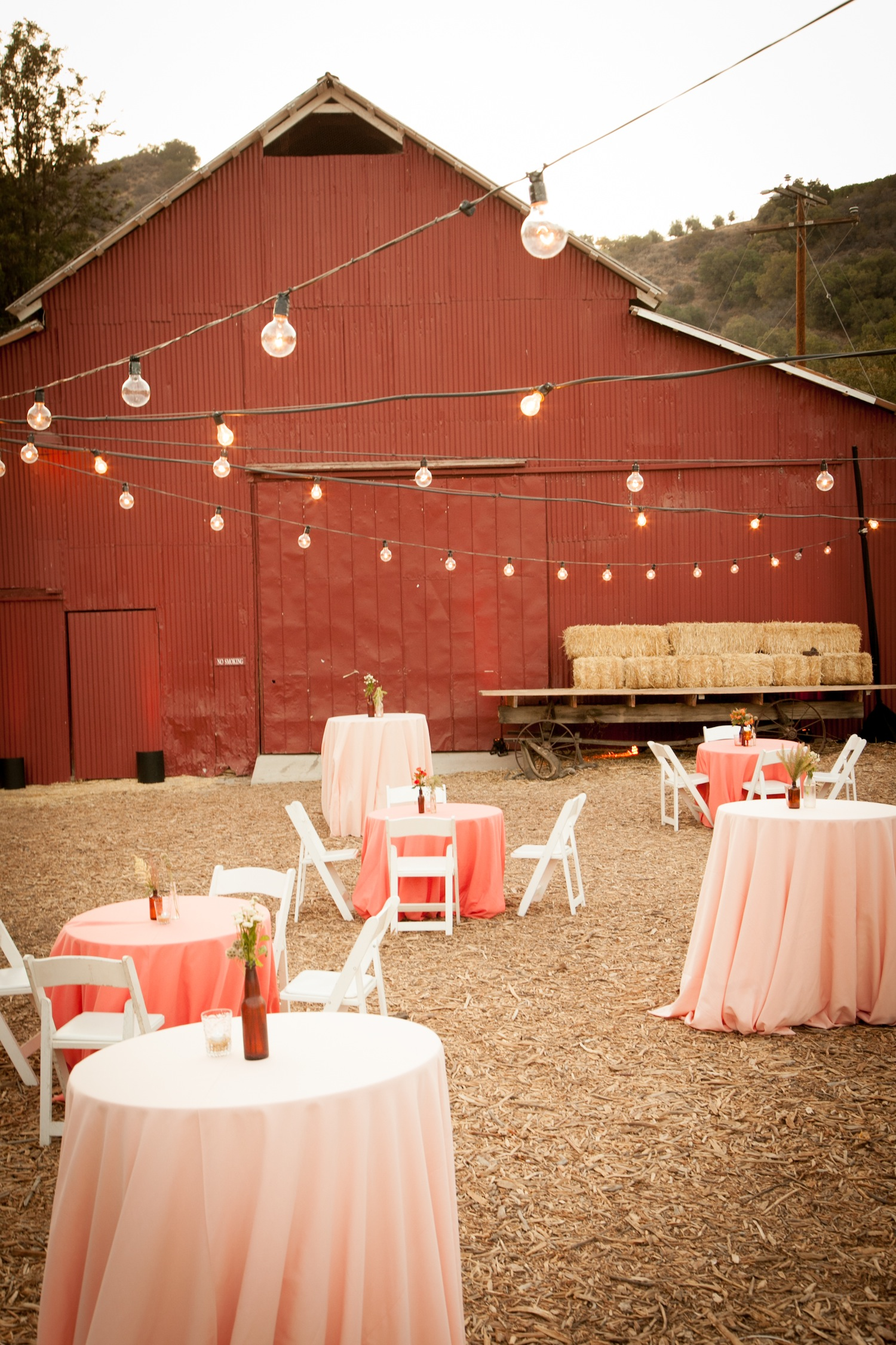 Red barn wedding cocktail hour pink tables David Tutera wedding