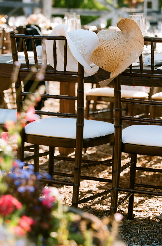 Rustic wedding chairs cowboy hats on bride and groom's chairs