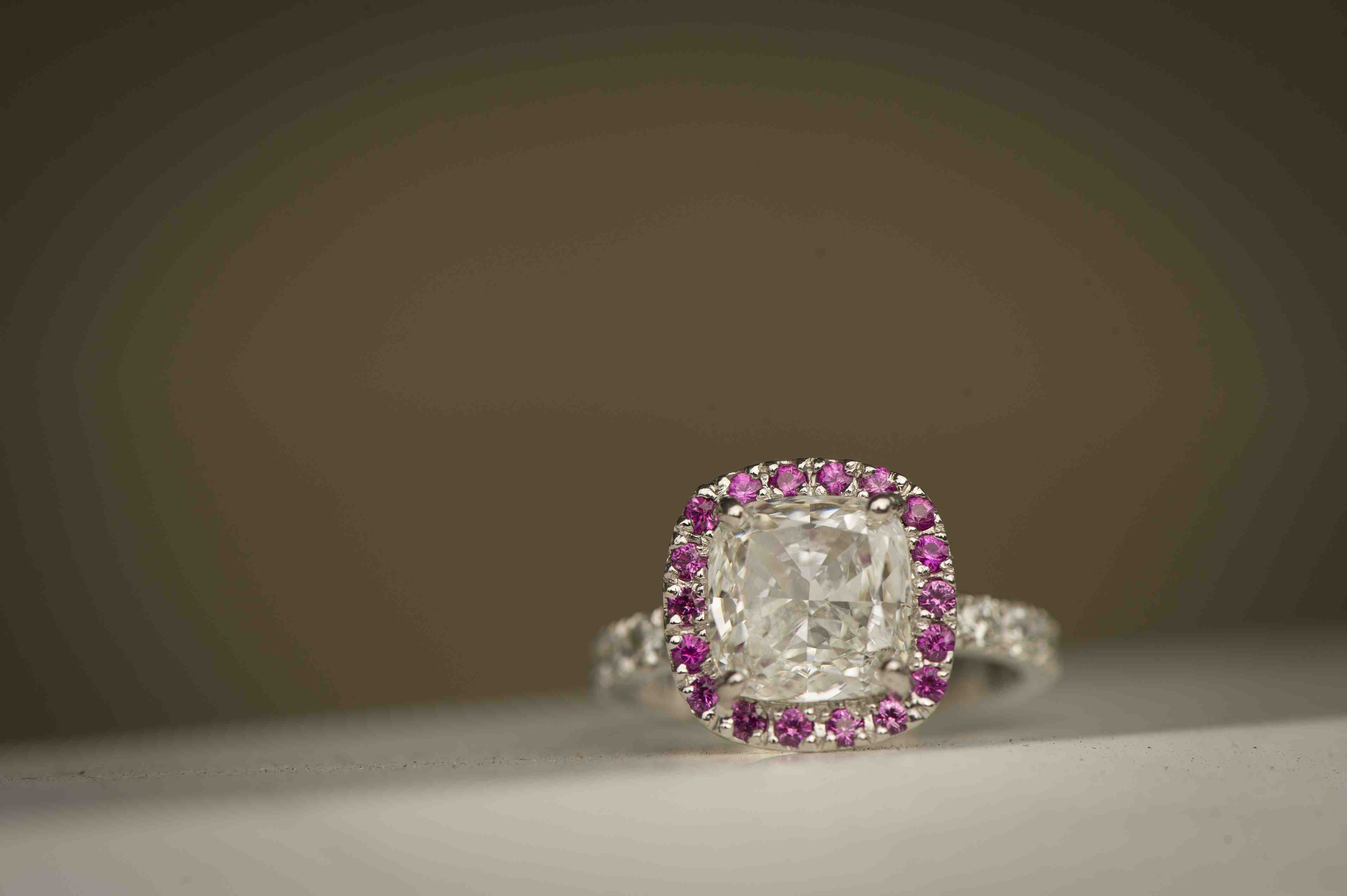 cushion cut diamond engagement ring with pink gemstone halo