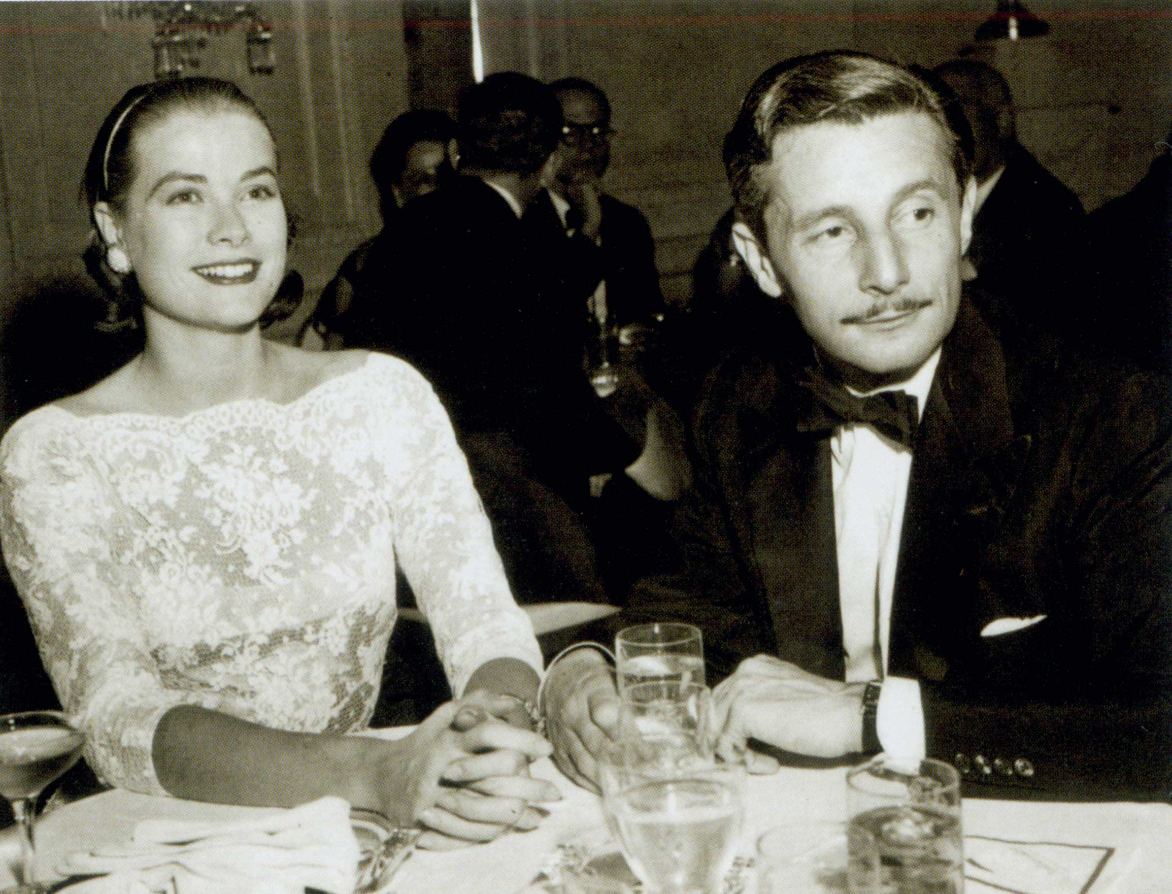 Grace Kelly in lace dress with Oleg Cassini at table