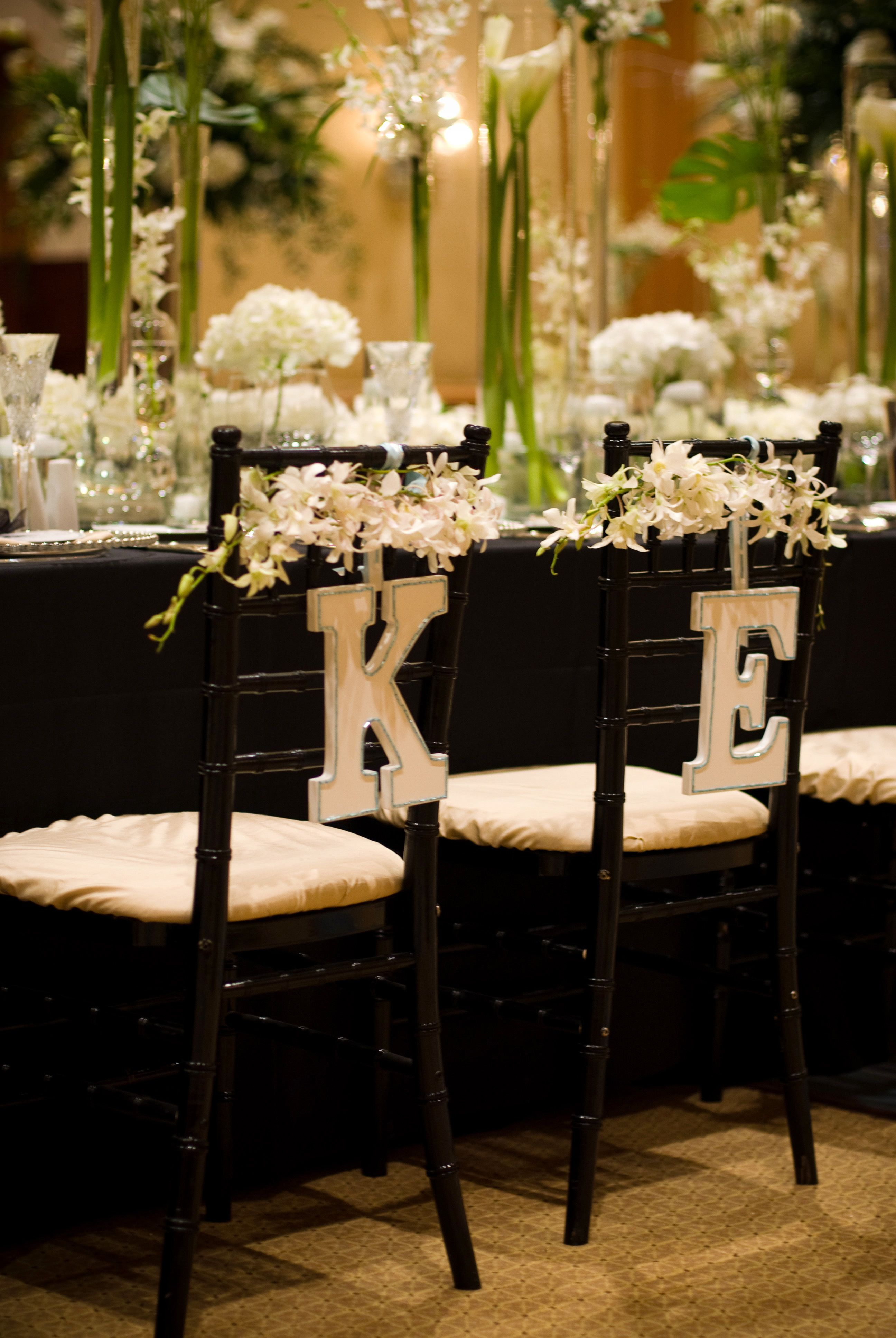 wooden initials signs hanging on bride and groom's chairs