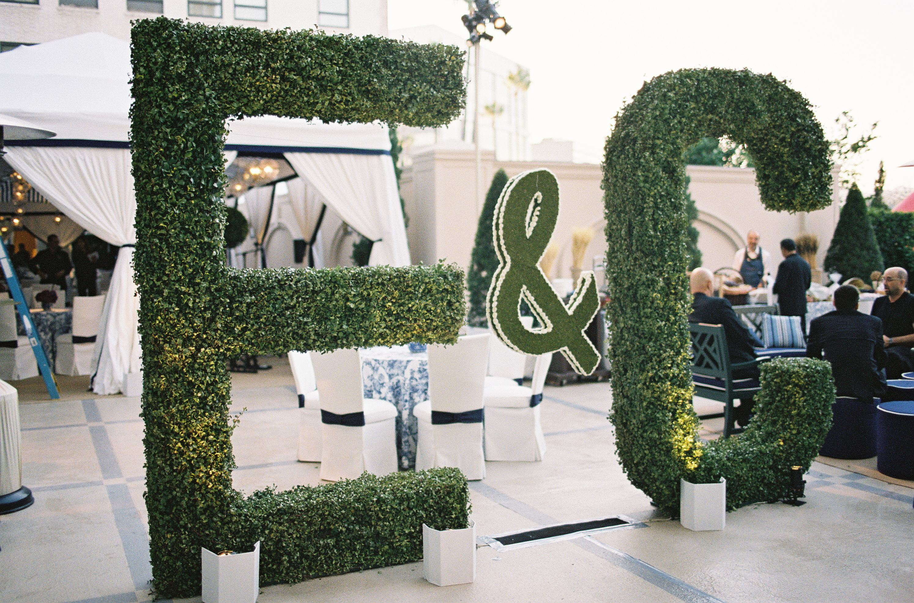 large topiary of initials at entrance of wedding rehearsal dinner