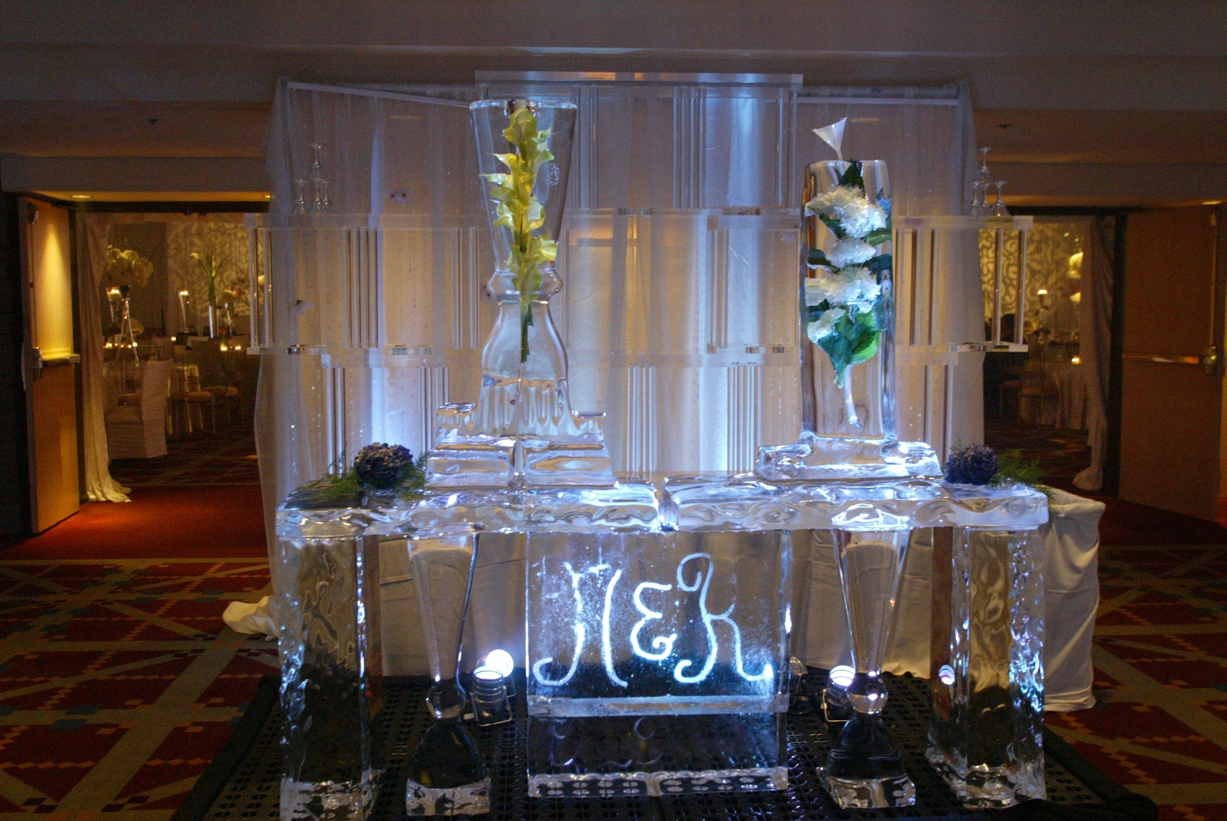 initials carved into ice sculpture at wedding