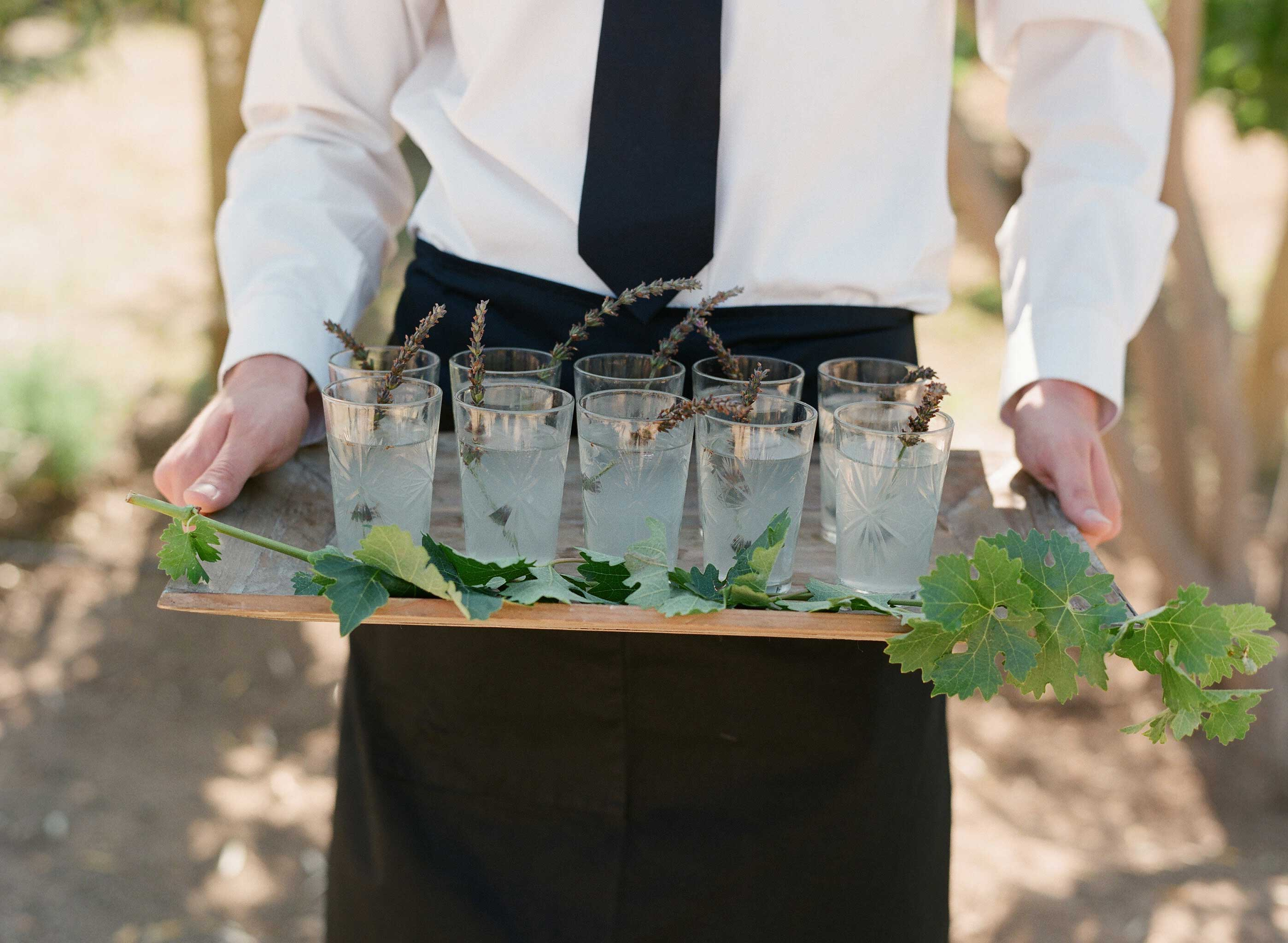 Server carrying wood tray with drinks lavender stirrers garnish