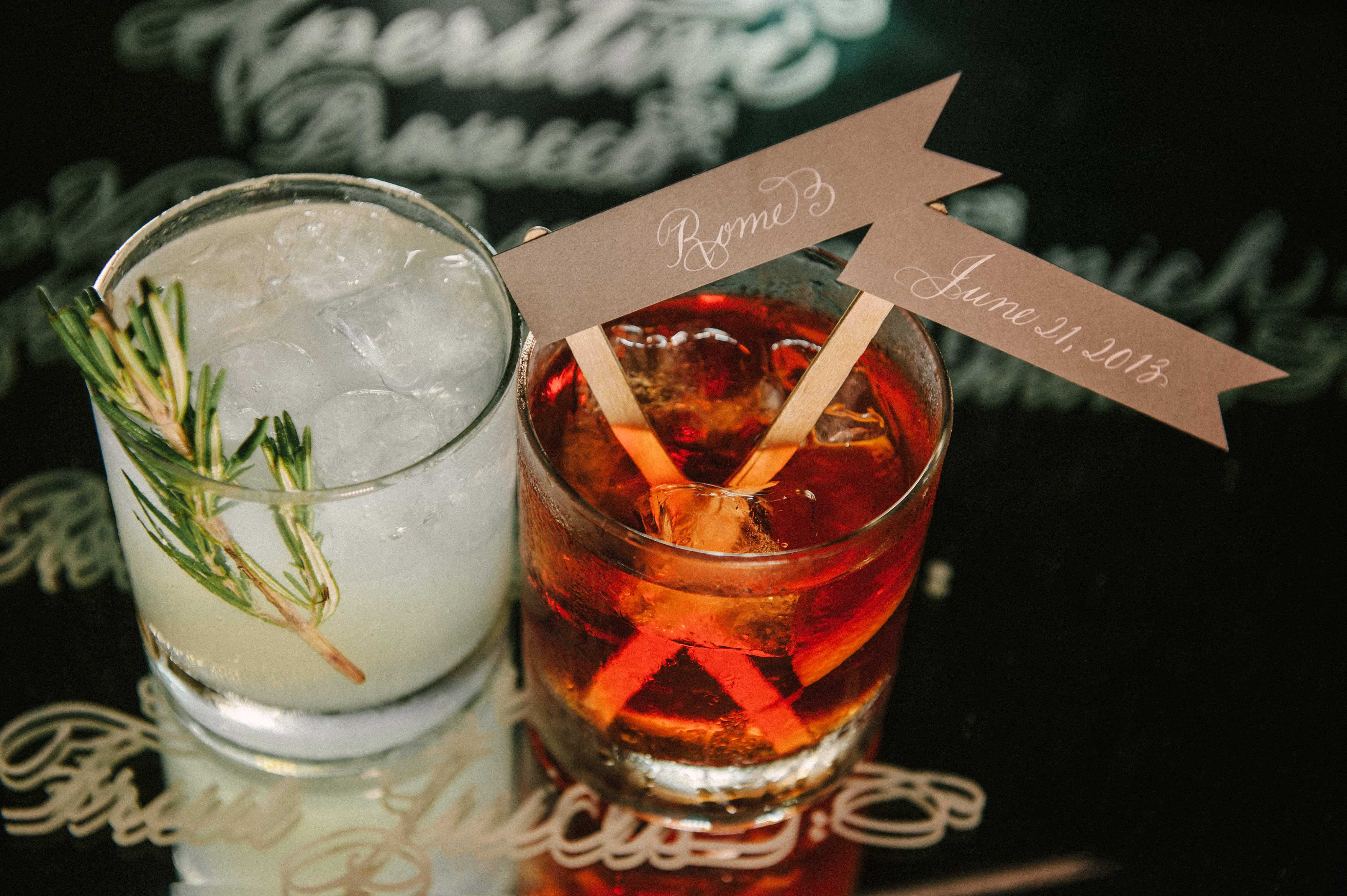 Cocktails with fresh herbs and drink stirrer with flag and location wedding date