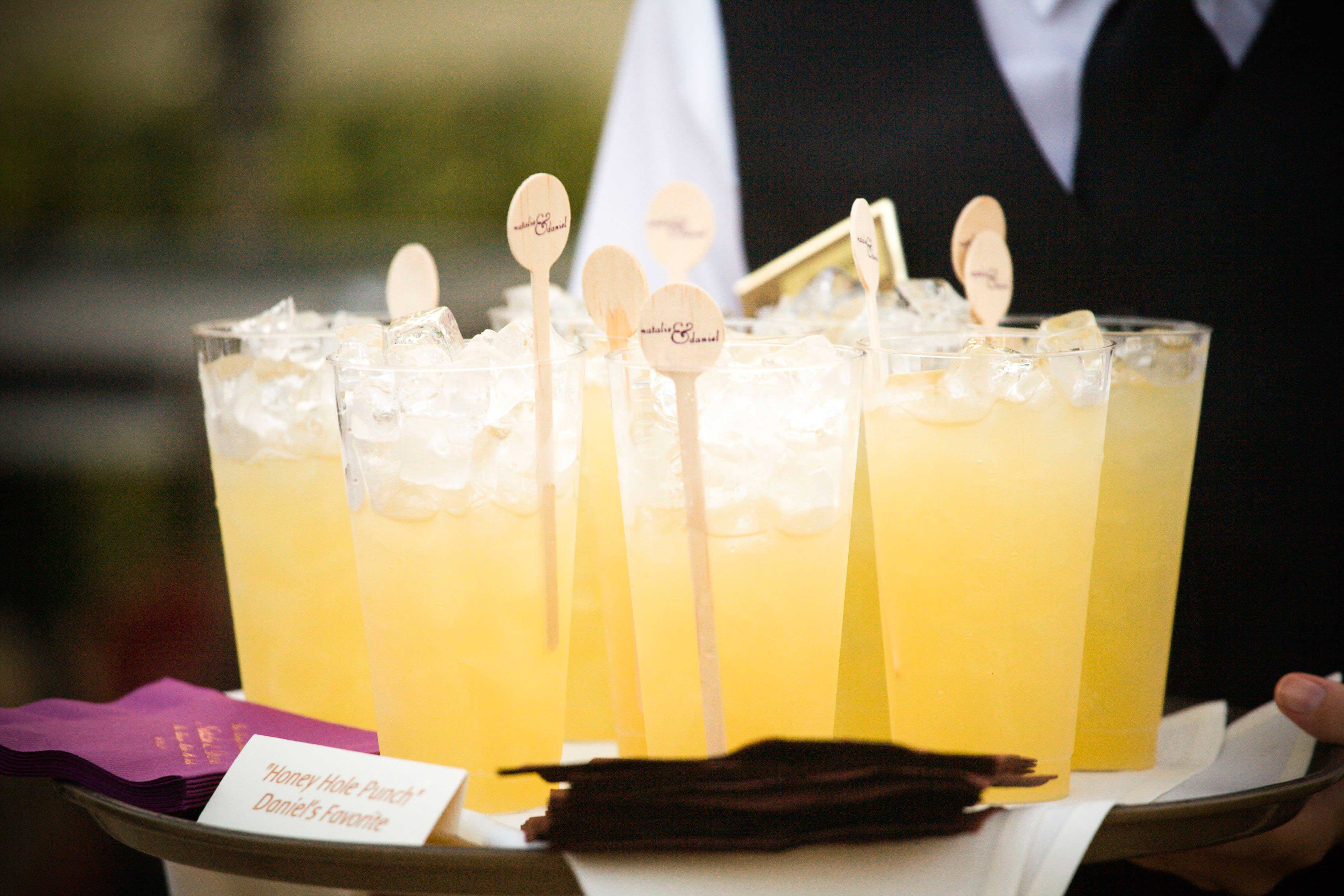 Wood drink stirrers with couple's names in yellow cocktails