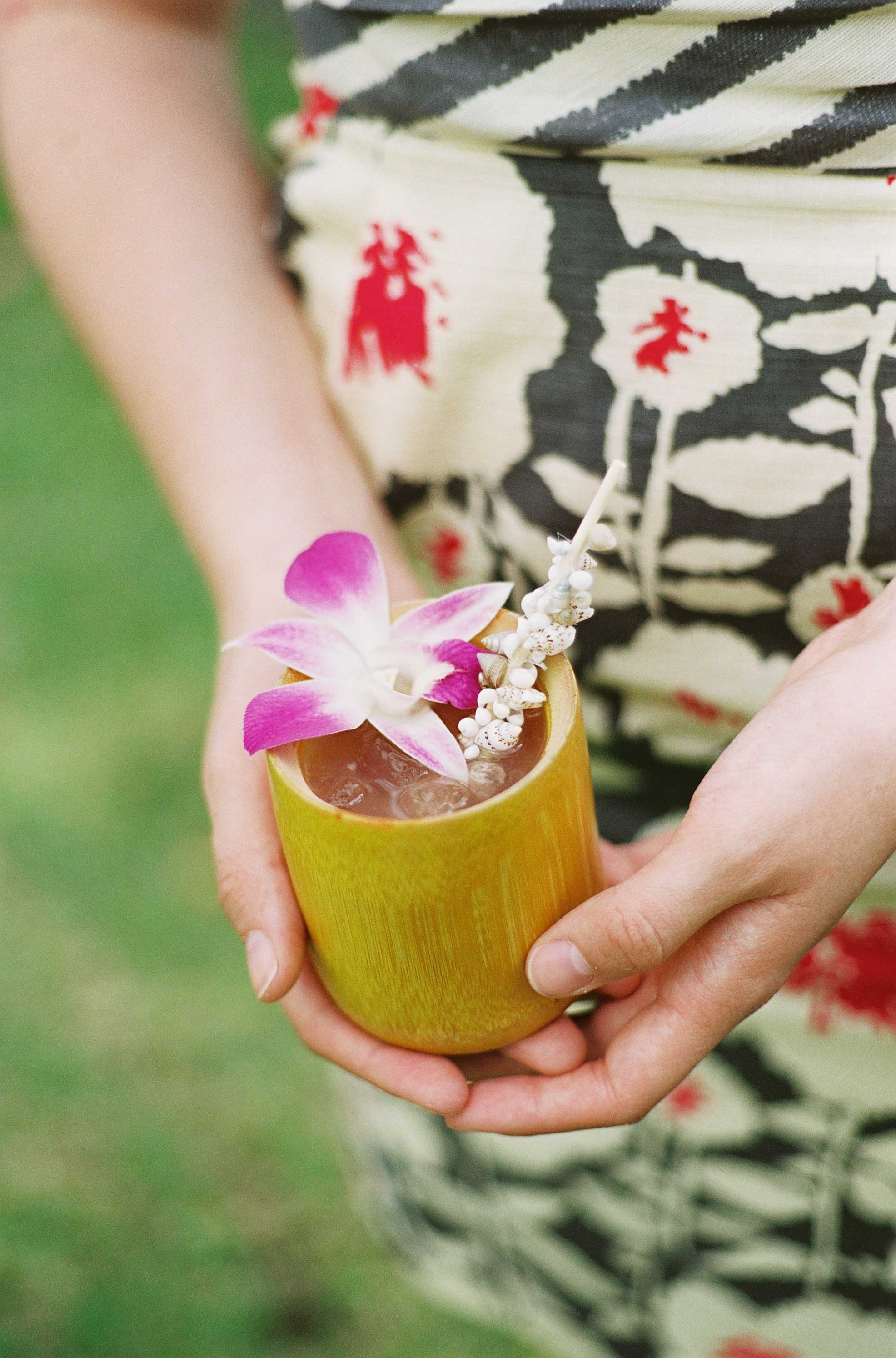 Destination wedding in Hawaii cocktail with orchid lei and seashell drink stirrer