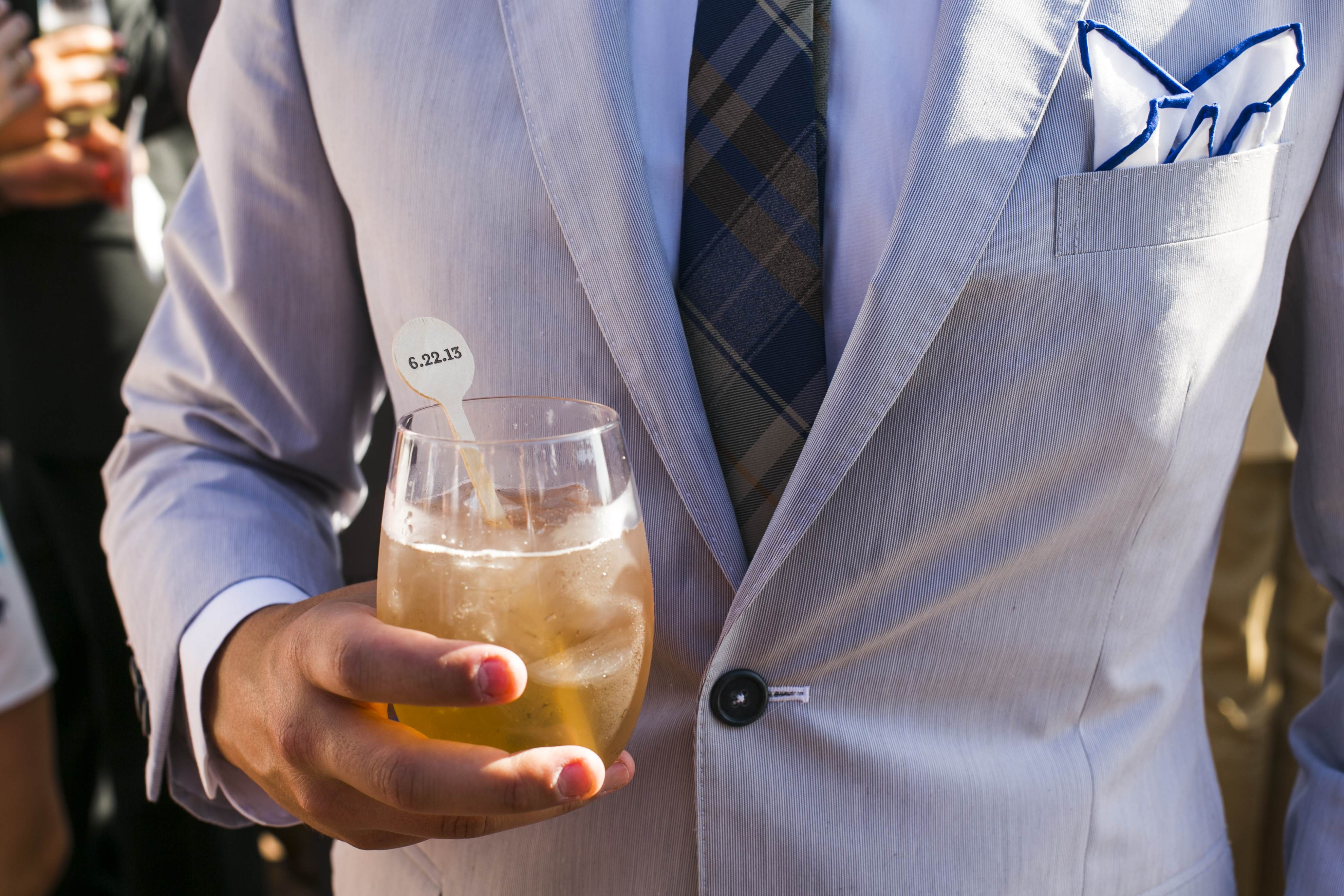 Guest in blue suit with cocktail and wood drink stirrer with wedding date