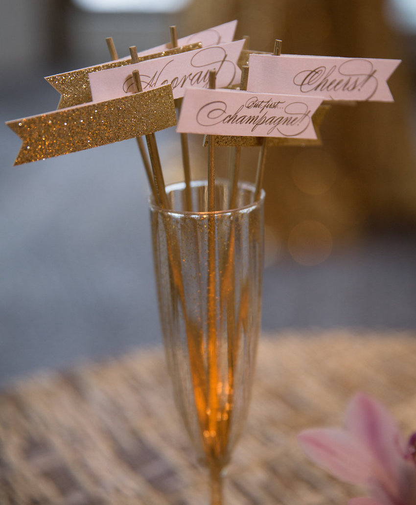 Champagne flute filled with glitter and pink drink stirrer flags with but first, champagne words