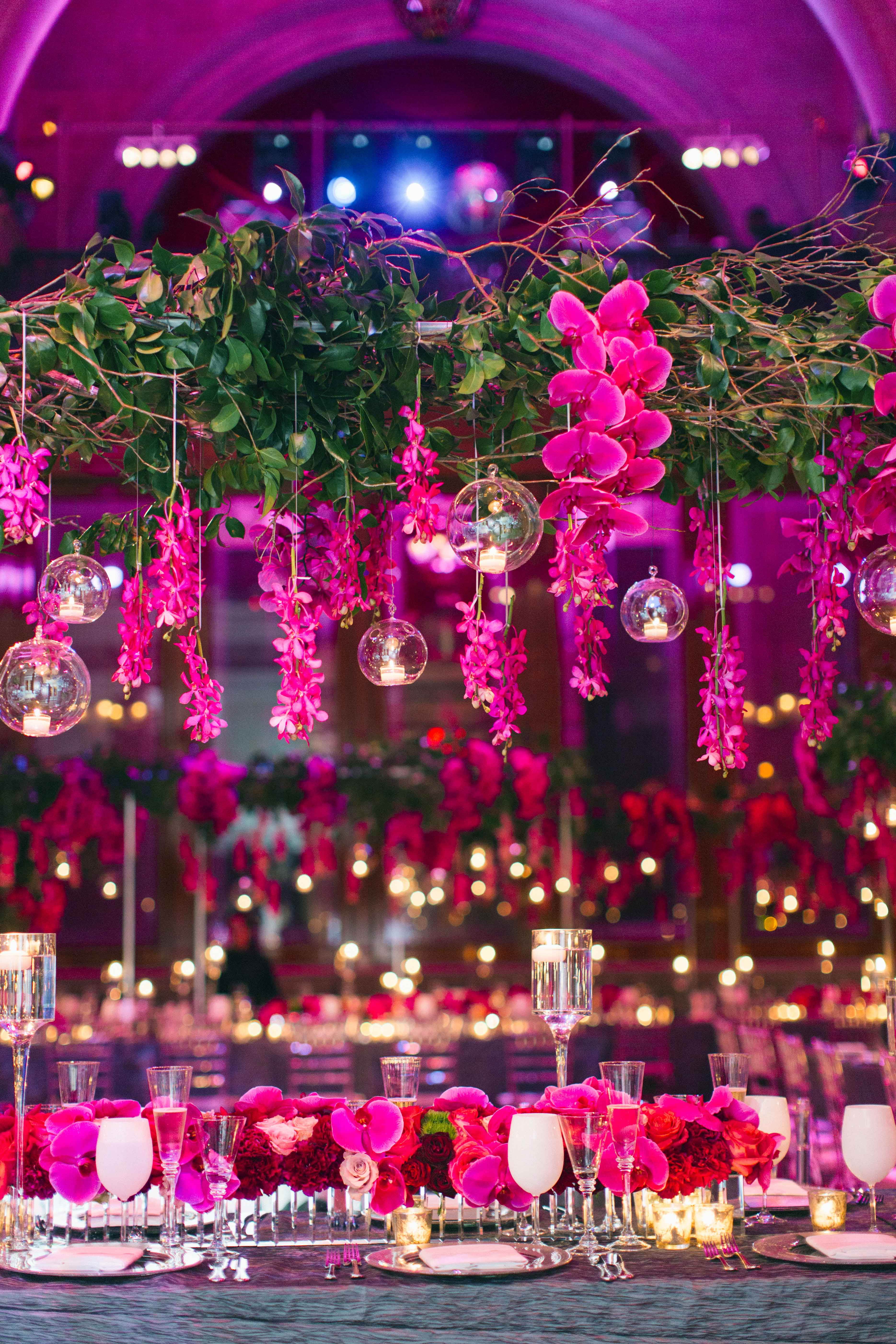Overhead wedding centerpiece fuchsia orchids, greenery, and glass globes with candles
