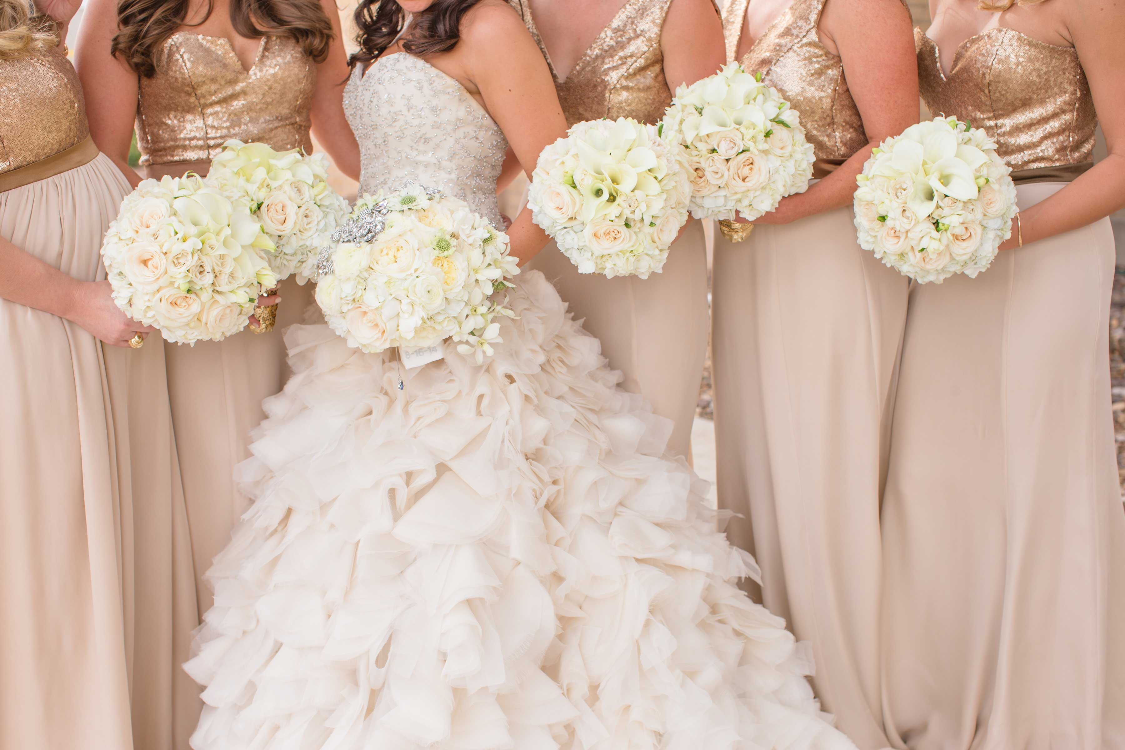 Bridesmaids in gold sequin bodice gowns with champagne skirts and bride in ruffled wedding dress